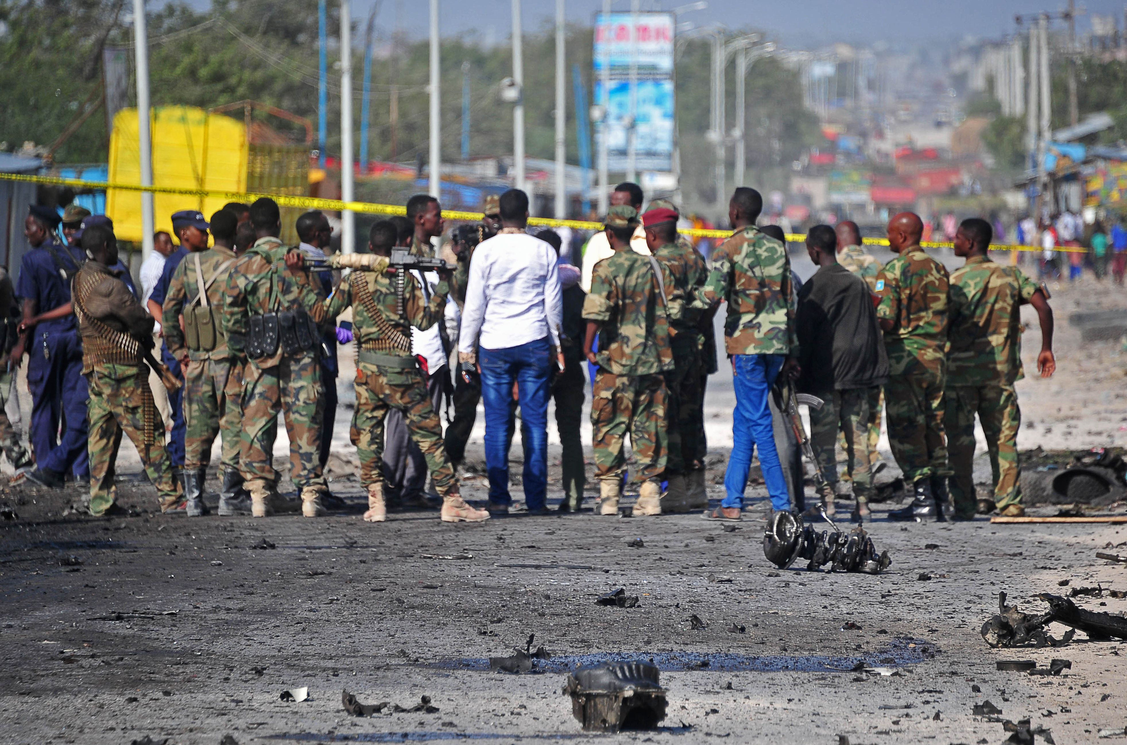 Members of the Somalian military forces stand at the site of a suicide car bomb attack, which killed a top Somalia general near Mogadsihu, Somalia, on Sept. 18, 2016