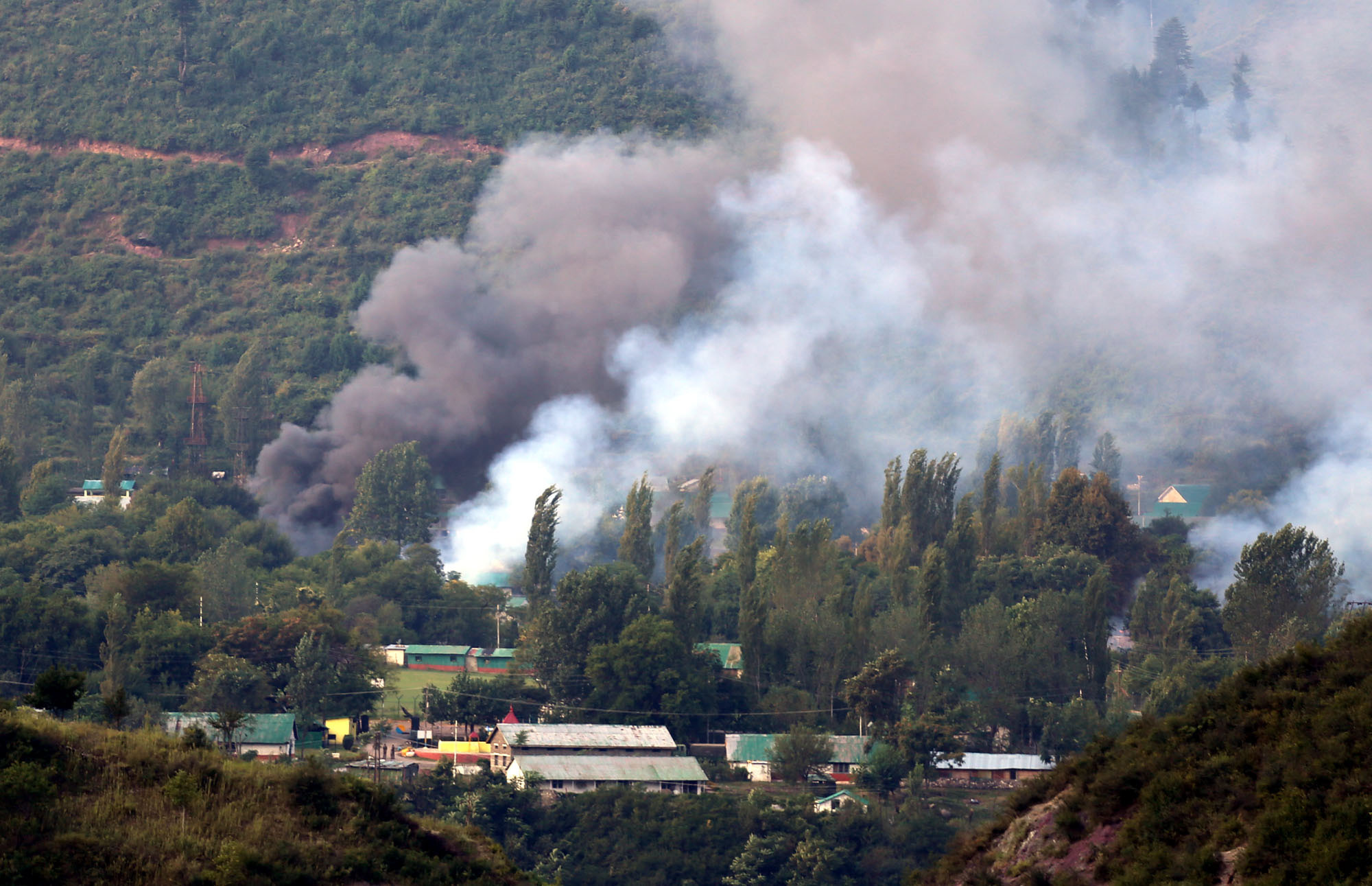 Smoke rises from the army base which was attacked by militants in the town of Uri, west of Srinagar, on September 18, 2016 in Srinagar, India.