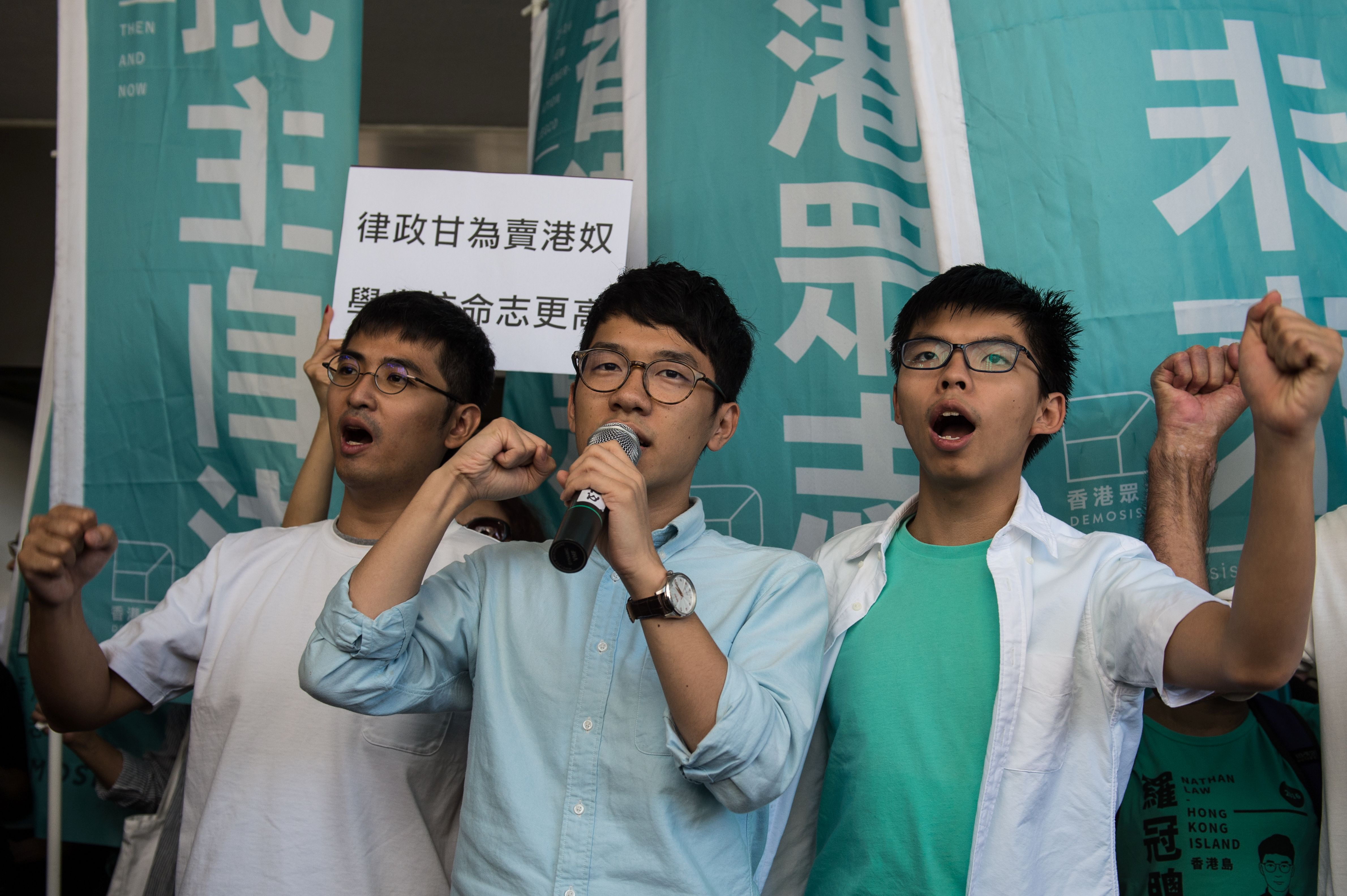 Leaders of Hong Kong's Umbrella Revolution, from left, Alex Chow, Nathan Law and Joshua Wong shout slogans as they arrive at the Eastern Court in Hong Kong on Sept. 21, 2016