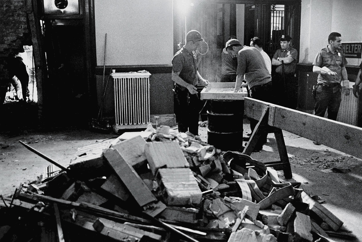 Construction workers and policemen stand around a pile of rubble in the police headquarters building after a bombing by the Weathermen Underground Organization, an offshoot of the SDS, New York, June 9, 1970.