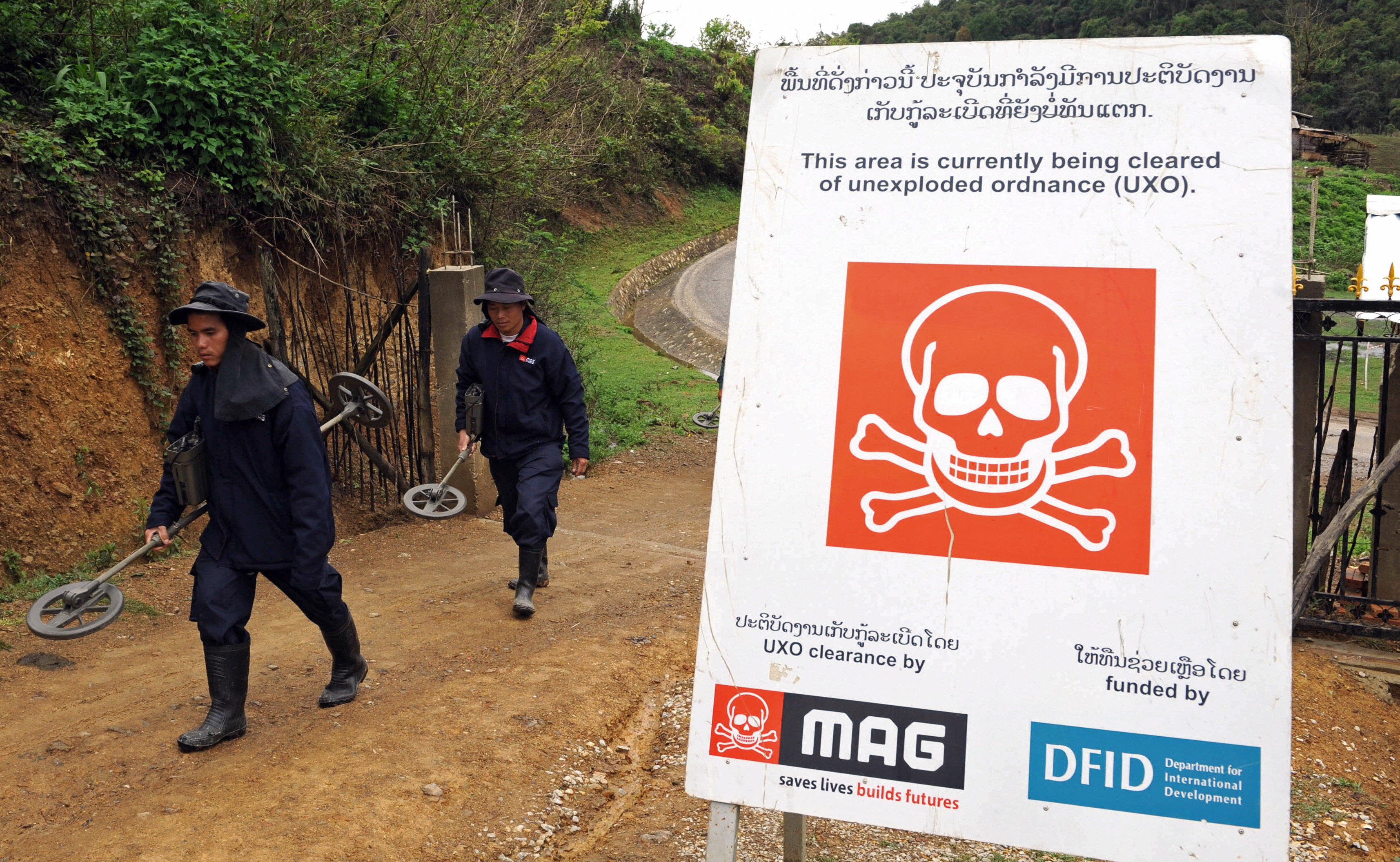 Workers of an UXO (unexploded ordnance) clearance team arrive at the Phuckae secondary school in the northern province of Xiangkhoang, Laos.