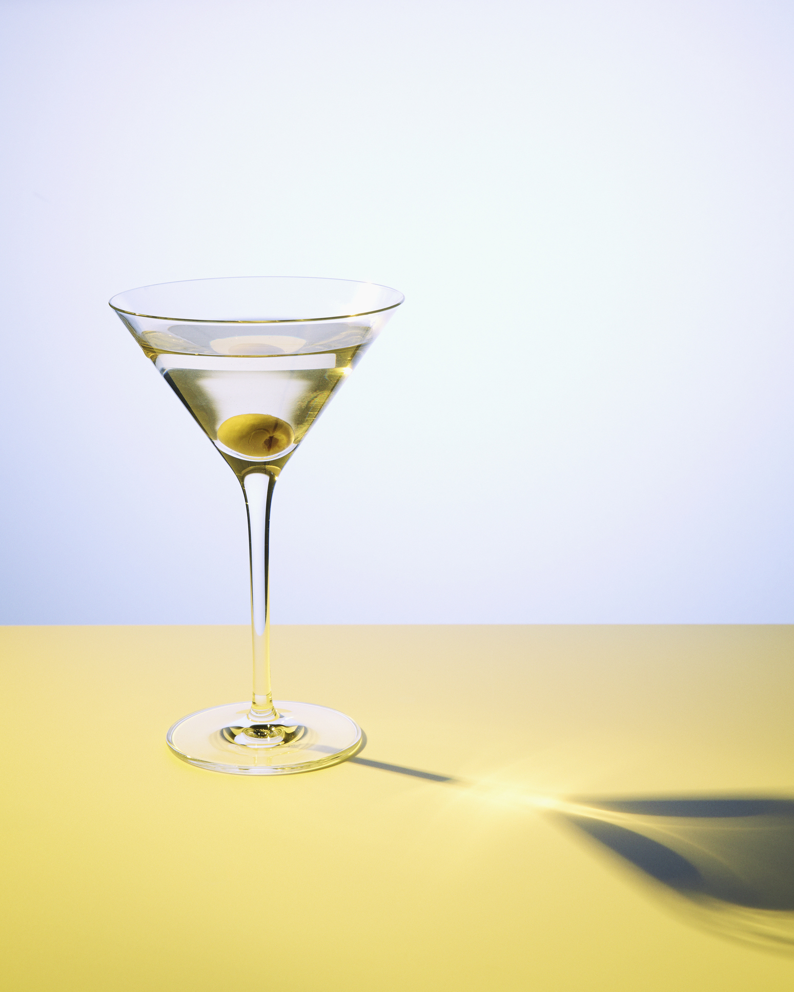 Martini cocktail in martini glass with an olive.  Studio shot.