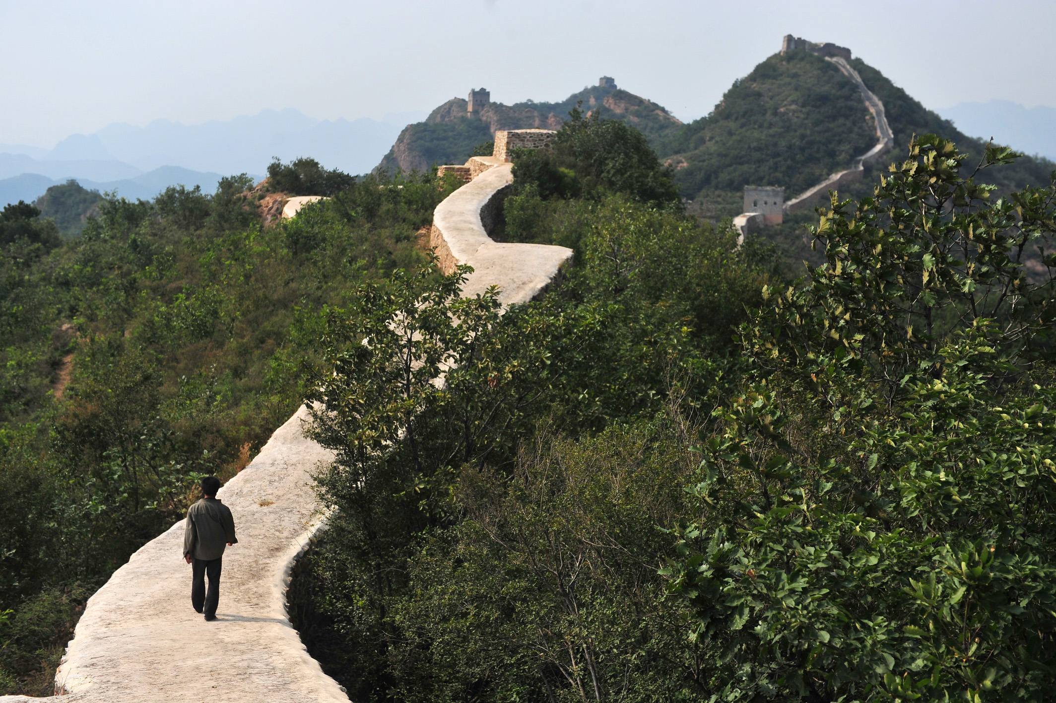 A Chinese farmer walks on a restored section of the Xiaohekou Great Wall, a wild stretch of the Great Wall, in Suizhong county, Huludao city, northeast China's Liaoning province, Sept. 21, 2016.