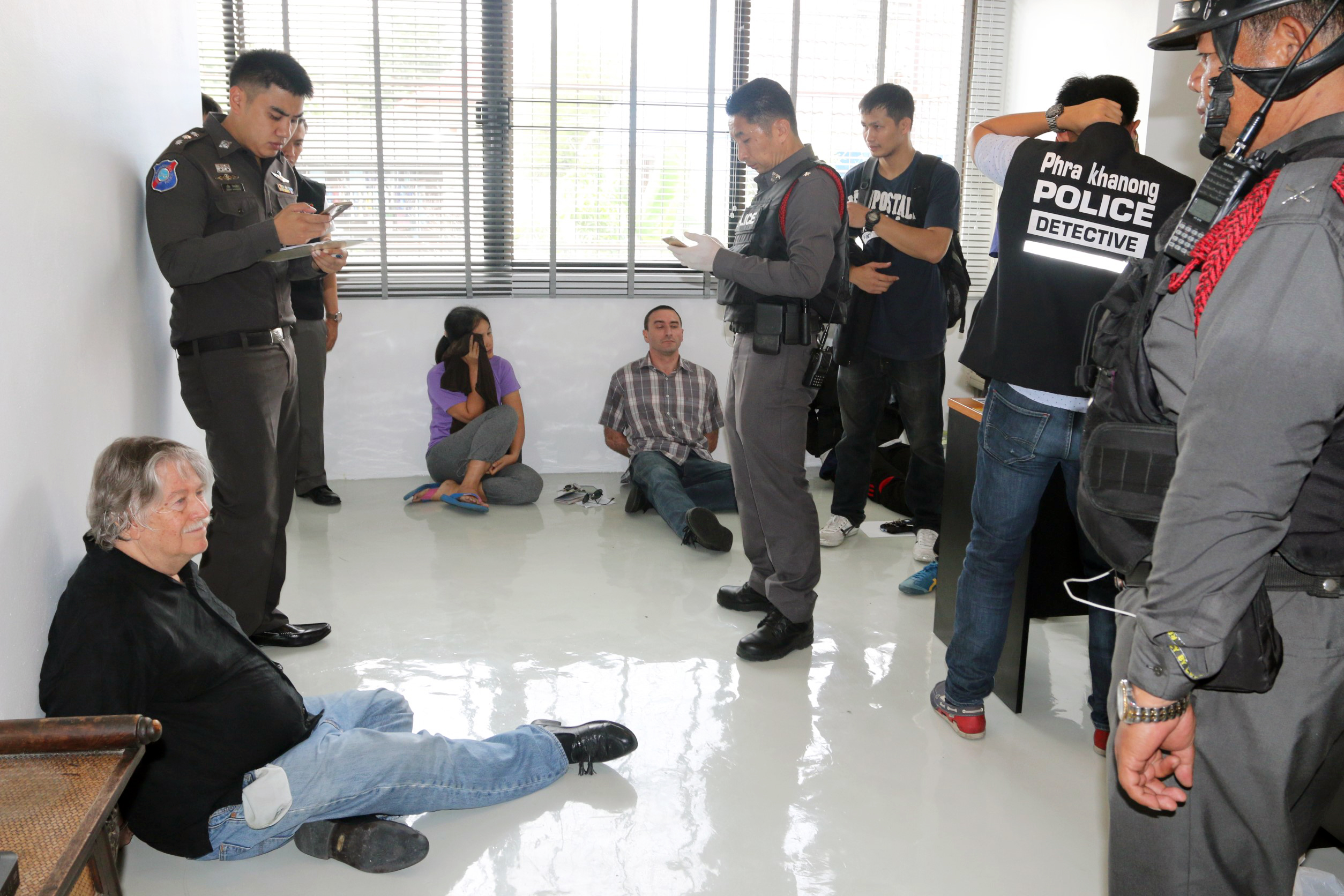 Thai police officers interrogate three foreigners arrested in an alleged passport-forgery operation in Bangkok on Sept. 23, 2016