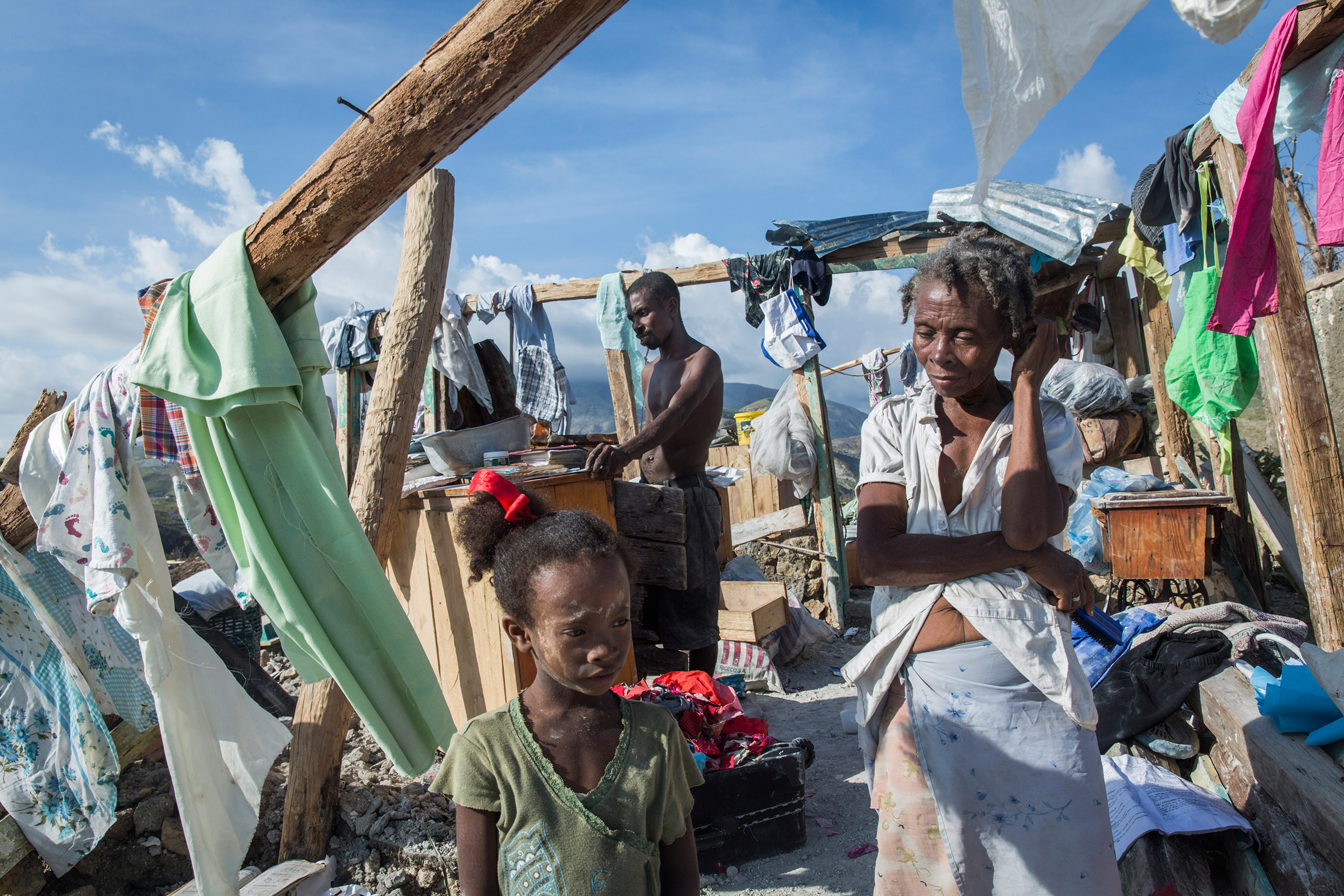 A family stands in the remains of their destroyed home in Roche-à-Bateau, southwestern Haiti, on Oct. 8, 2016. More than 1,000 people were reported killed by Hurricane Matthew, the worst storm to hit the island in more than 50 years.From  On the Ground in Hurricane-Wrecked Haiti