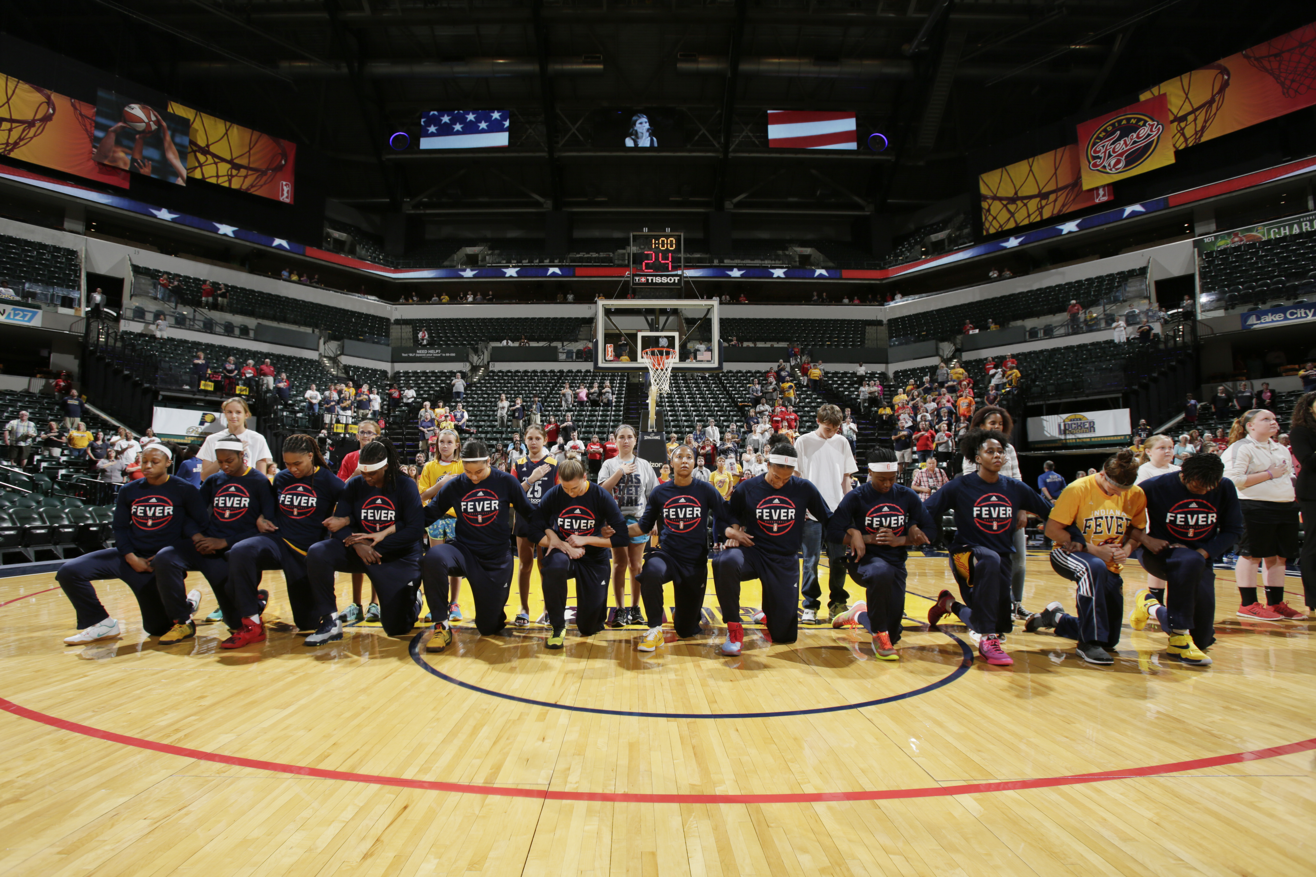 The Indiana Fever kneel during the National Anthem before the game against the Phoenix Mercury during Round One of the 2016 WNBA Playoffs on September 21, 2016 at Bankers Life Fieldhouse in Indianapolis, Indiana.