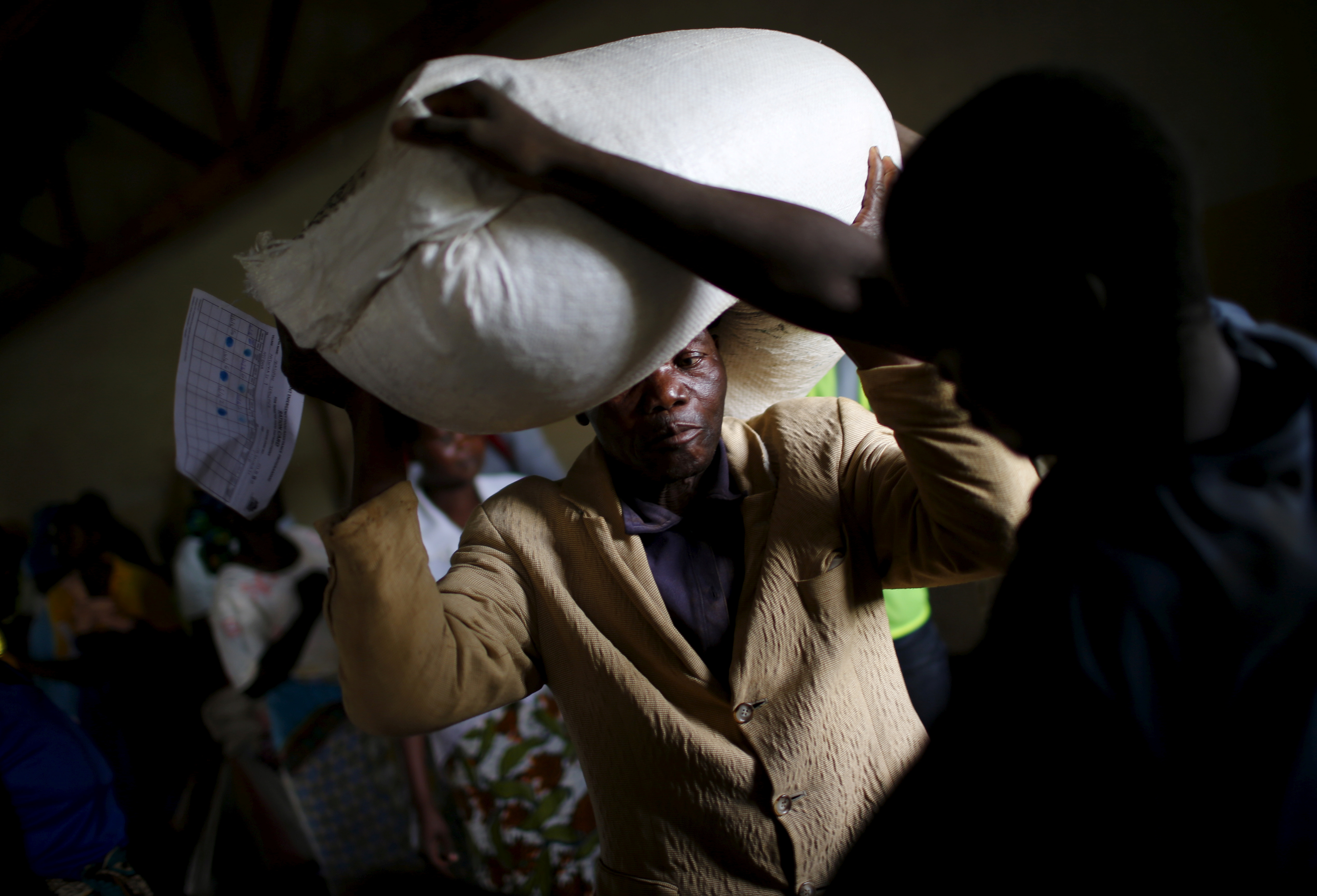 A man carries food aid distributed by the United Nations World Food Progamme (WFP) in Mzumazi village near Malawi's capital Lilongwe, Feb. 3, 2016.