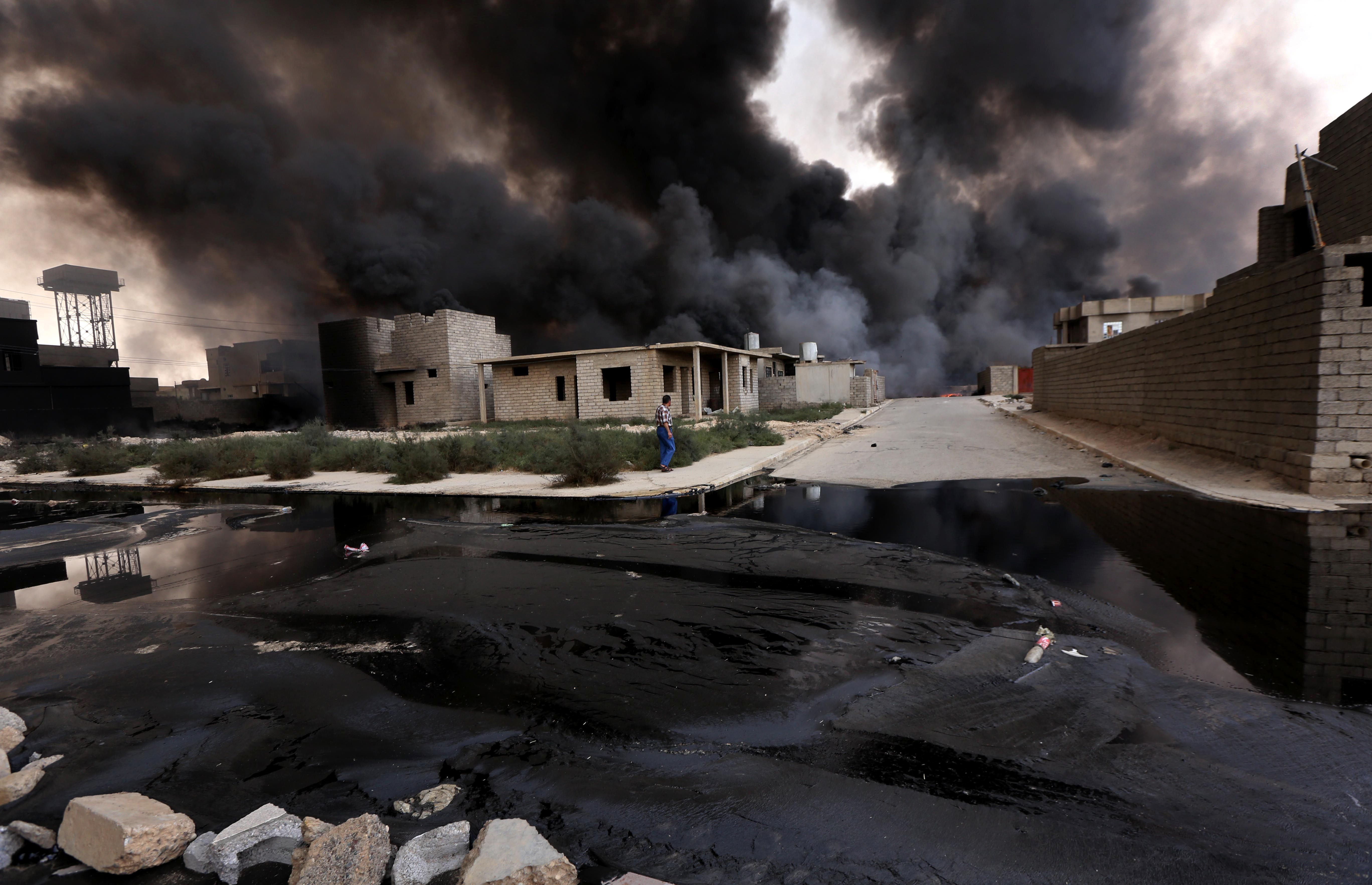 Smoke billows from oil wells, set ablaze by Islamic State militants before fleeing the Iraqi region of Qayyarah, on August 30, 2016.