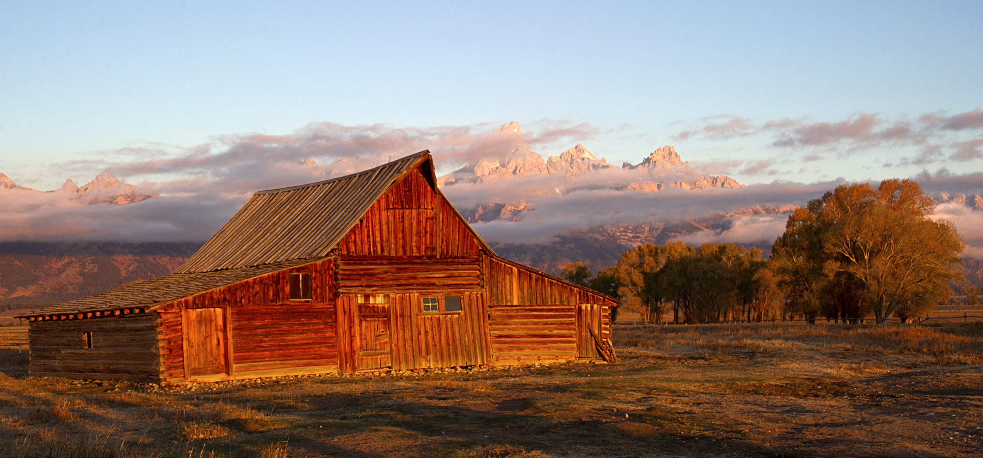 The sun hits the tips of the Grand Tetons behind the Moulton barn October 5, 2012 in the Grand Teton National Park in Wyoming. Grand Teton National Park is located in northwestern Wyoming. Approximately 310,000 acres (130,000 ha) in size, the park includes the major peaks of the 40-mile (64 km) long Teton Range as well as most of the northern sections of the valley known as Jackson Hole. AFP PHOTO/Karen BLEIER        (Photo credit should read KAREN BLEIER/AFP/Getty Images)