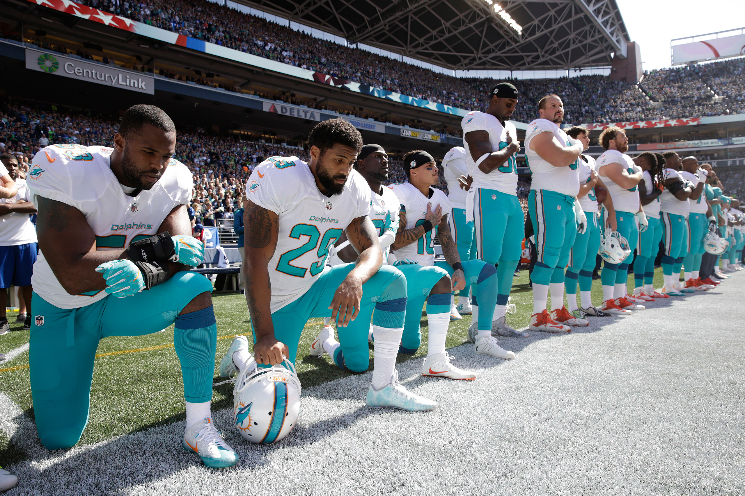 Jelani Jenkins, Arian Foster, Michael Thomas, and Kenny Stills of the Miami Dolphins kneel during the singing of the national anthem before a game against the Seattle Seahawks in Seattle on Sept. 11, 2016.