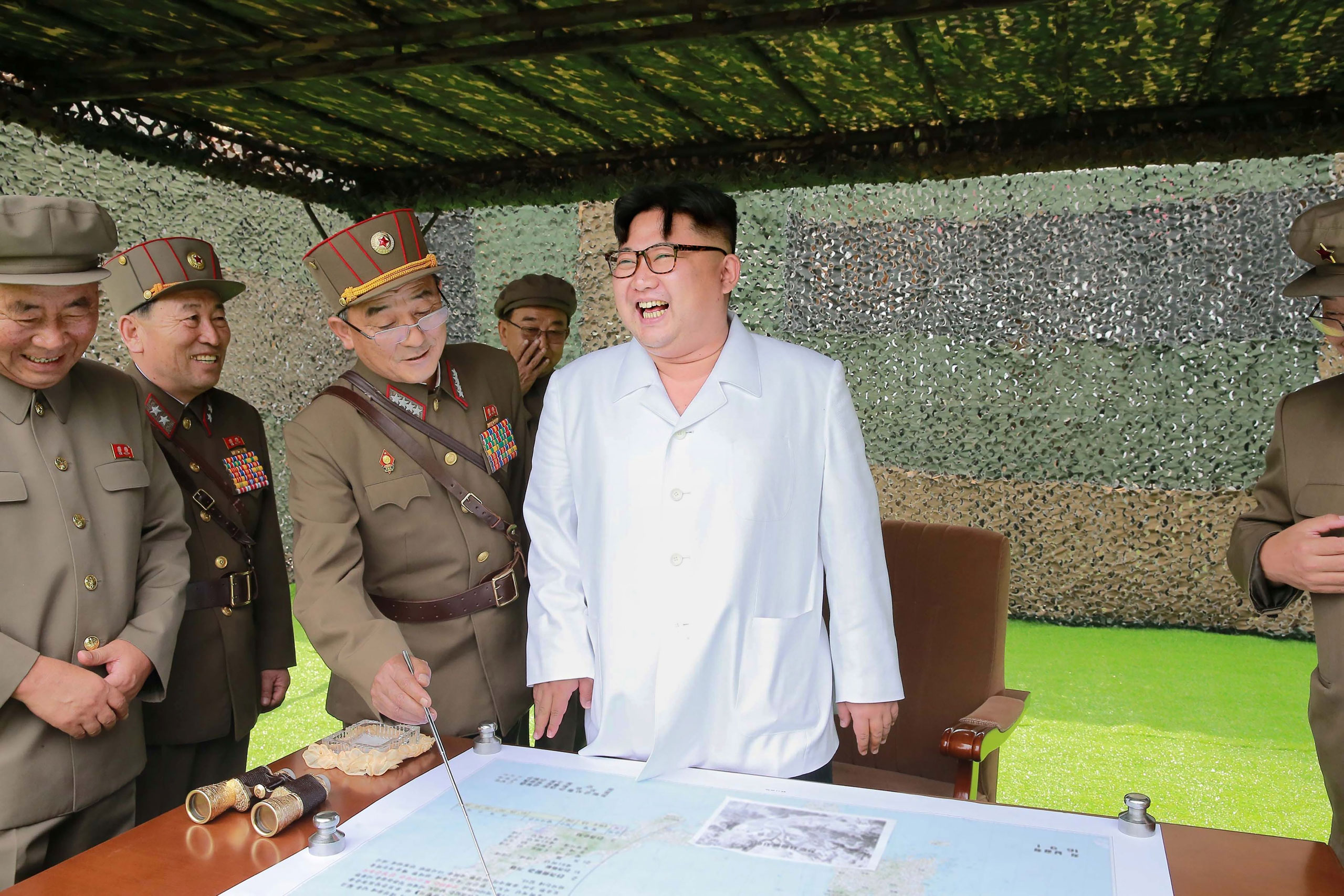 North Korean leader Kim Jong Un confers with his generals during a demonstration of ballistic missiles