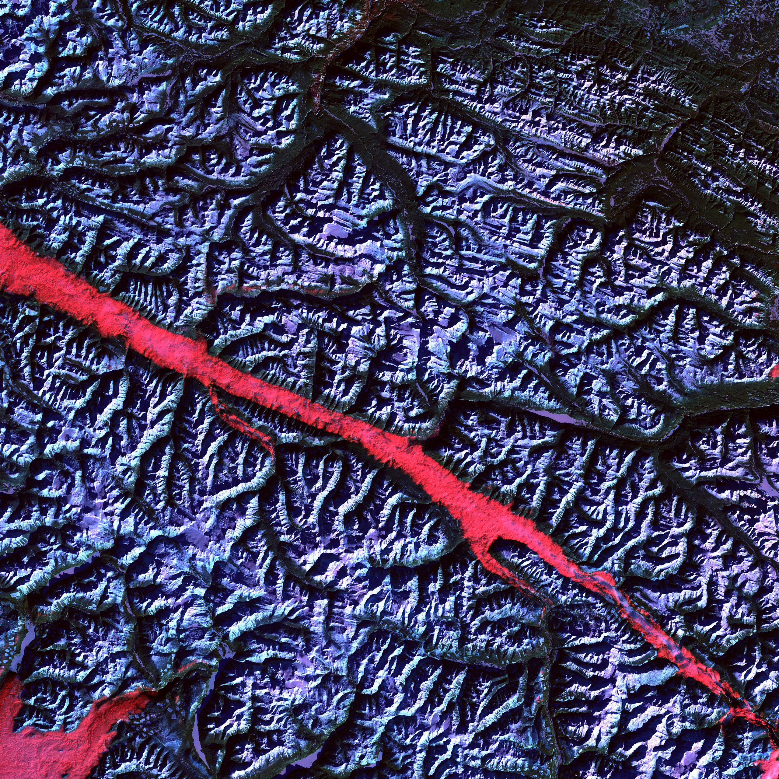 Rocky Mountain Trench, CanadaThe high reflectance of clouds compared to the surrounding land, coupled with the low sun elevation when this image was acquired, causes low clouds to appear red as they fill a portion of the trench. February 2004.
