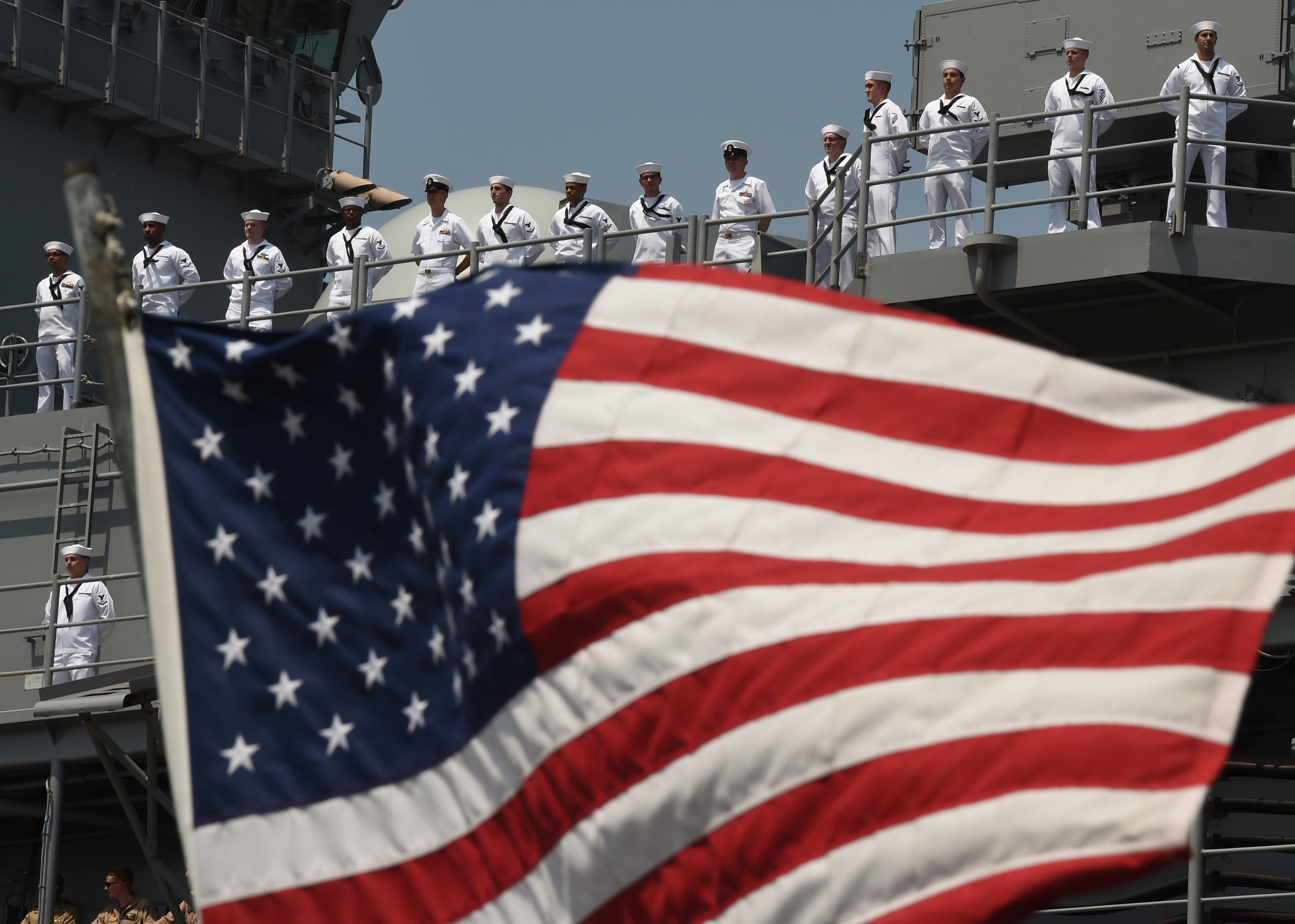 The US Flag blows in the wind as sailors and marines stand on the deck of the USS Bataan as it arrives into Pier 88  during the 'Parade of Ships' in New York, on May 25, 2016.