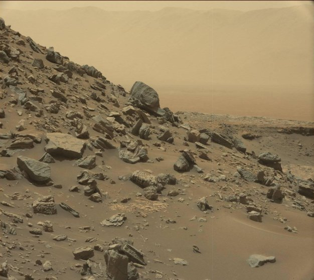 The rim of Gale Crater is visible in the distance, through the dusty haze, in this Curiosity view of a sloping hillside on Mount Sharp.
