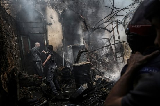 Firefighters extinguish flames following an airstrike by forces loyal to the Syrian government in the rebel-held area of Douma, on the outskirts of Damascus, on Sept. 11, 2016.