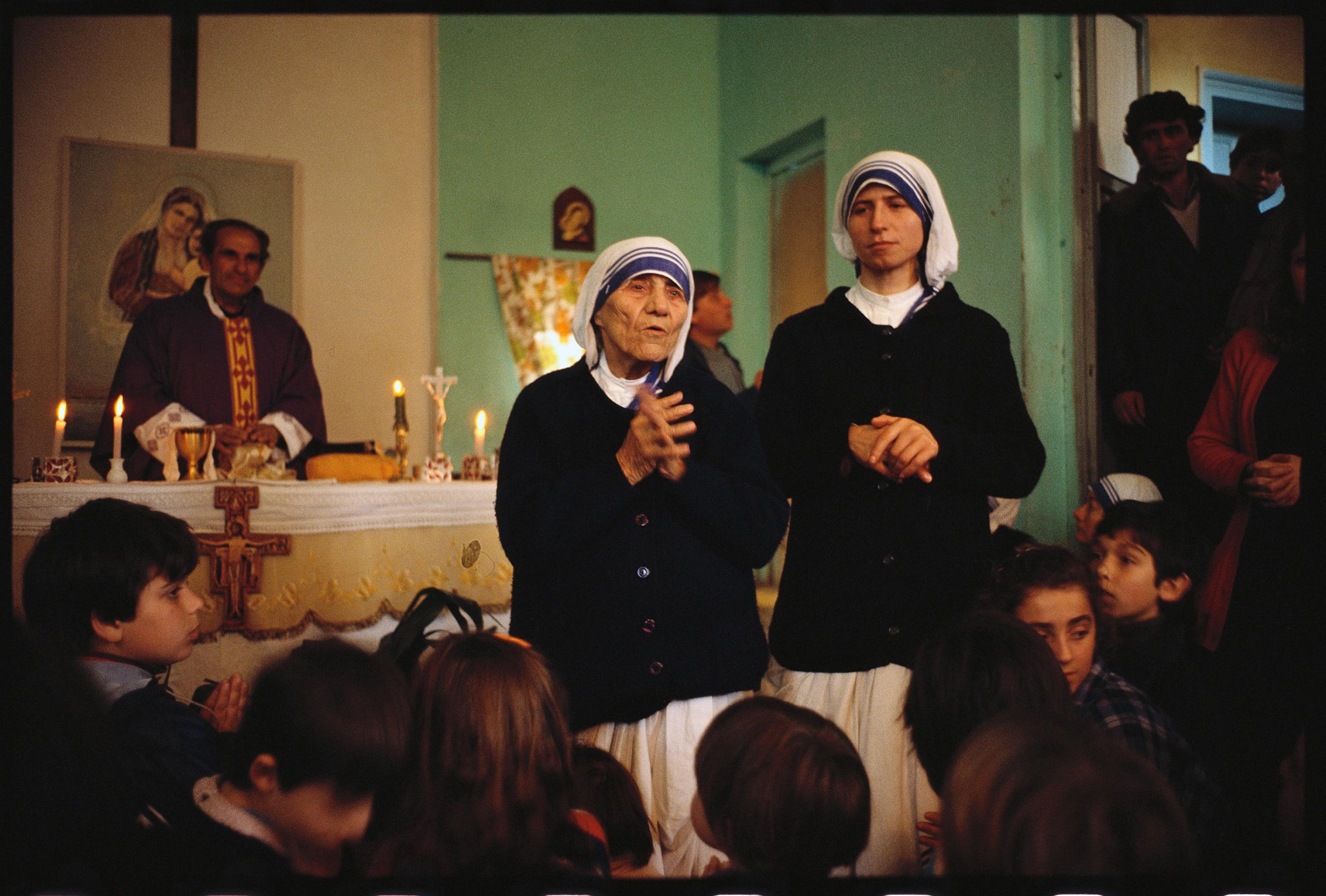 Mother Teresa addresses a group of children during mass at a church.