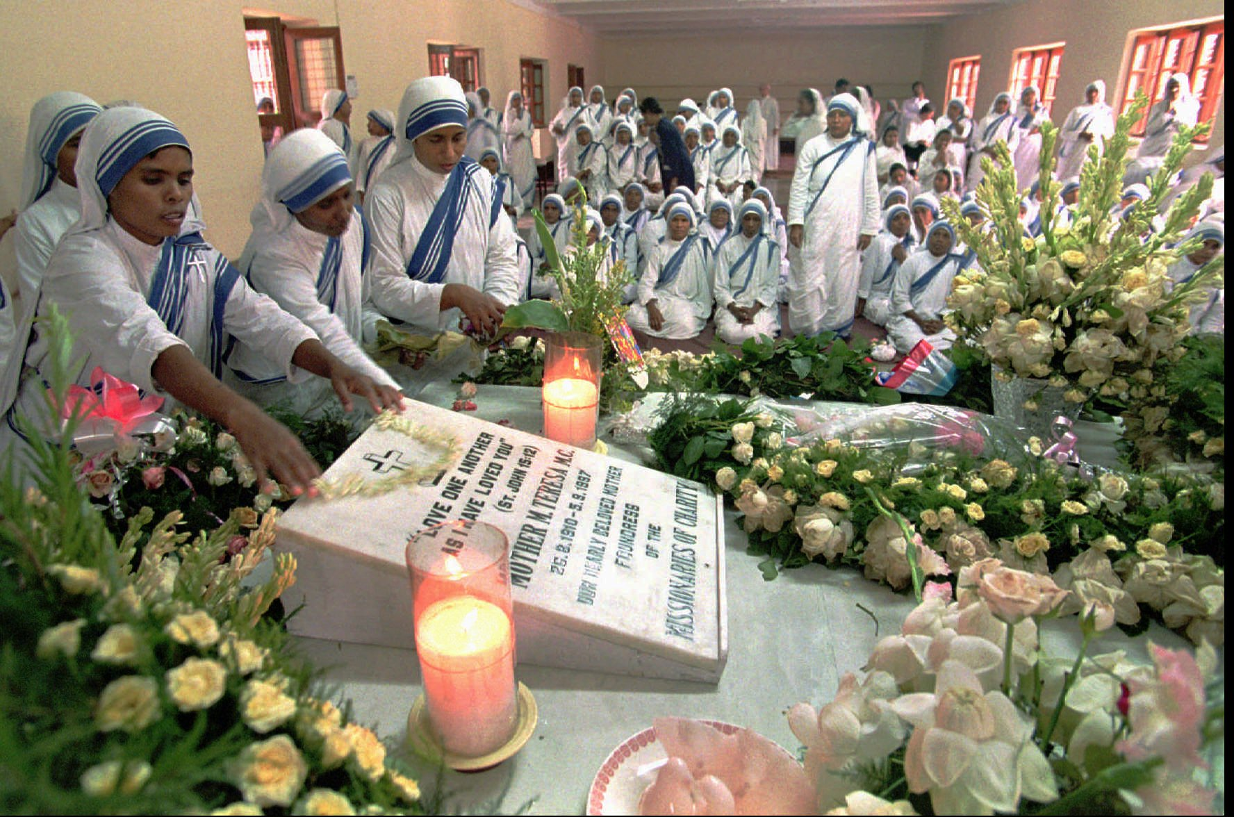 Sisters of the Missionaries of Charity decorate the tomb of Mother Teresa, who was buried after a state funeral, at Mother House in Calcutta, India, on Sept. 14, 1997.