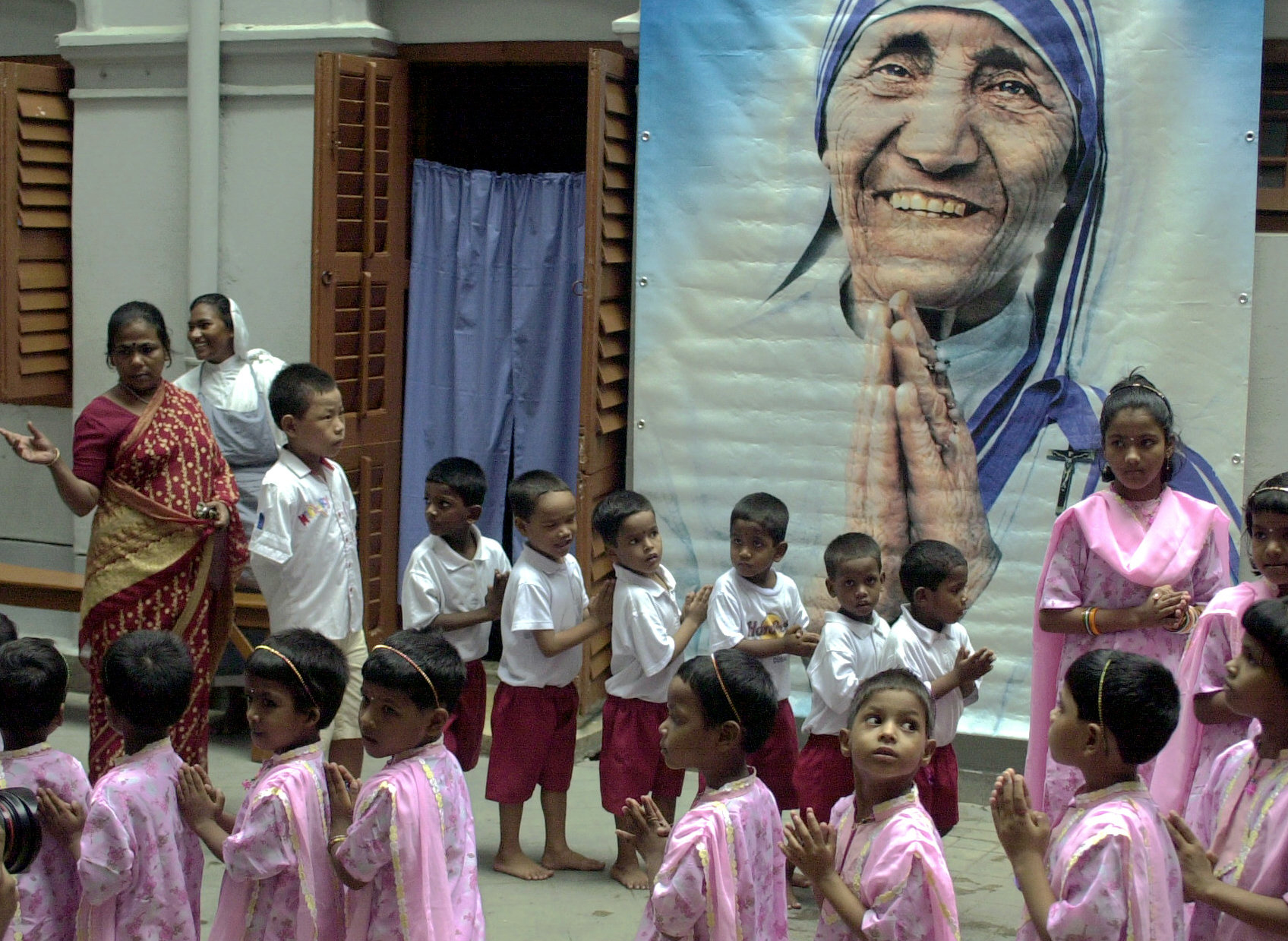 A group of Indian orphans along with a nun of the Missionaries of Charity offer prayers in front of a portrait of Mother Teresa during prayers to observe the seventh anniversary of her death in Calcutta, Sept. 5, 2004.