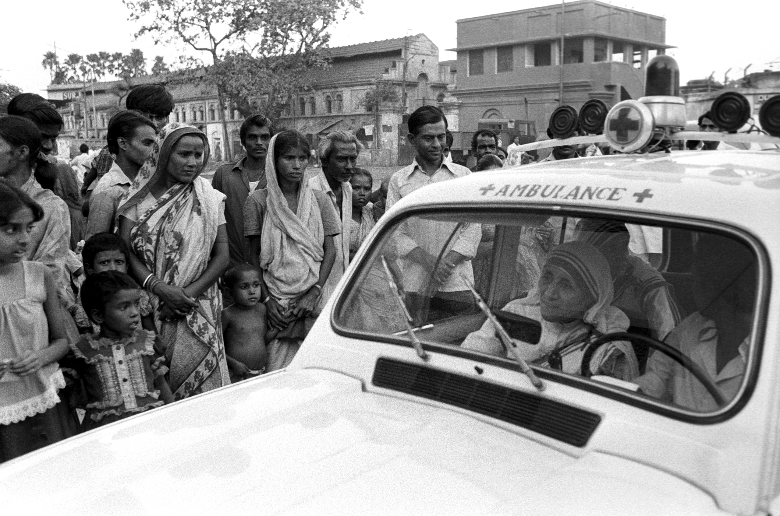 Mother Teresa rides in an ambulance alongside a group of impoverished people in Calcutta, India, in October 1979.