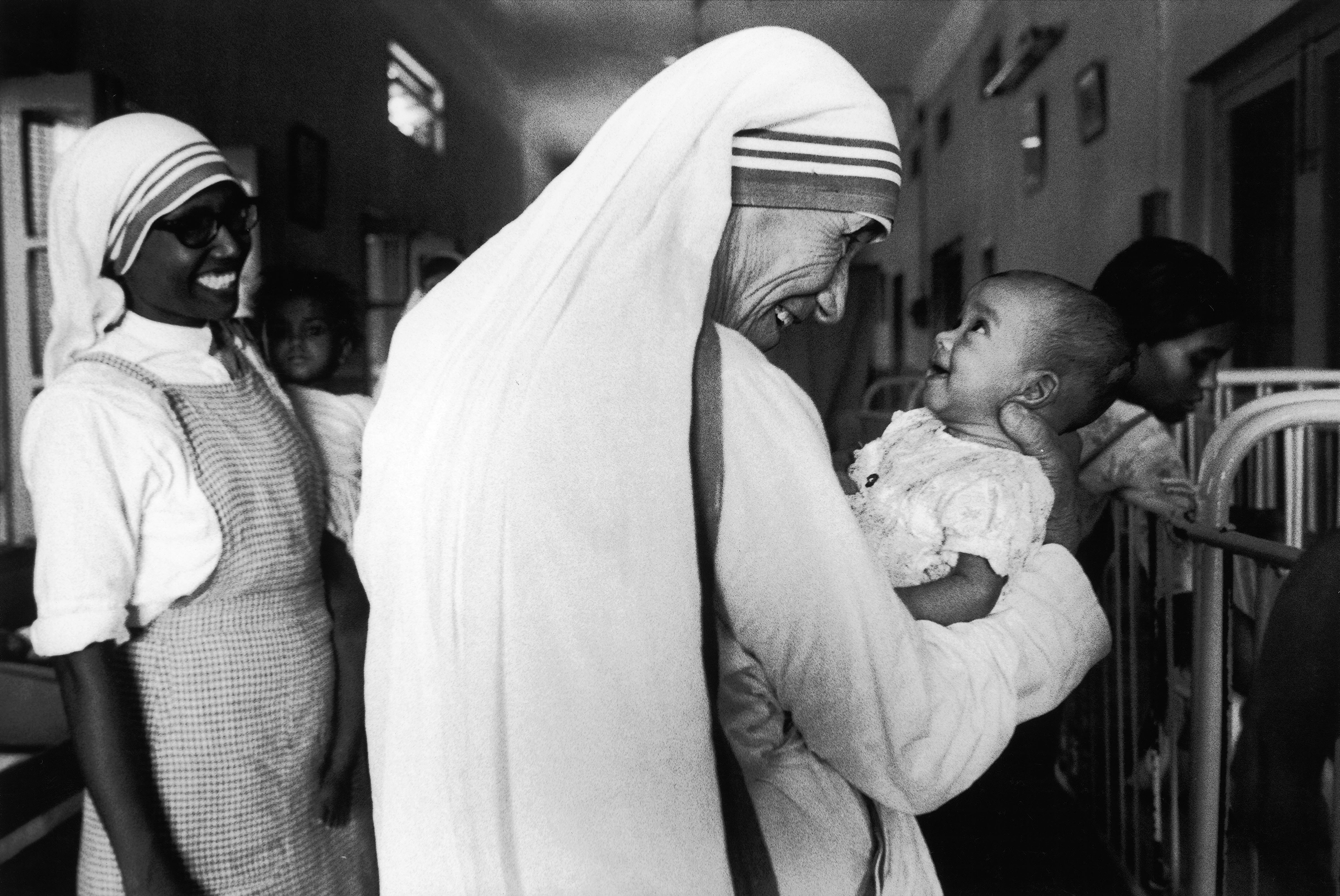 Mother Teresa smiles with an infant in Calcutta, India, in 1981.