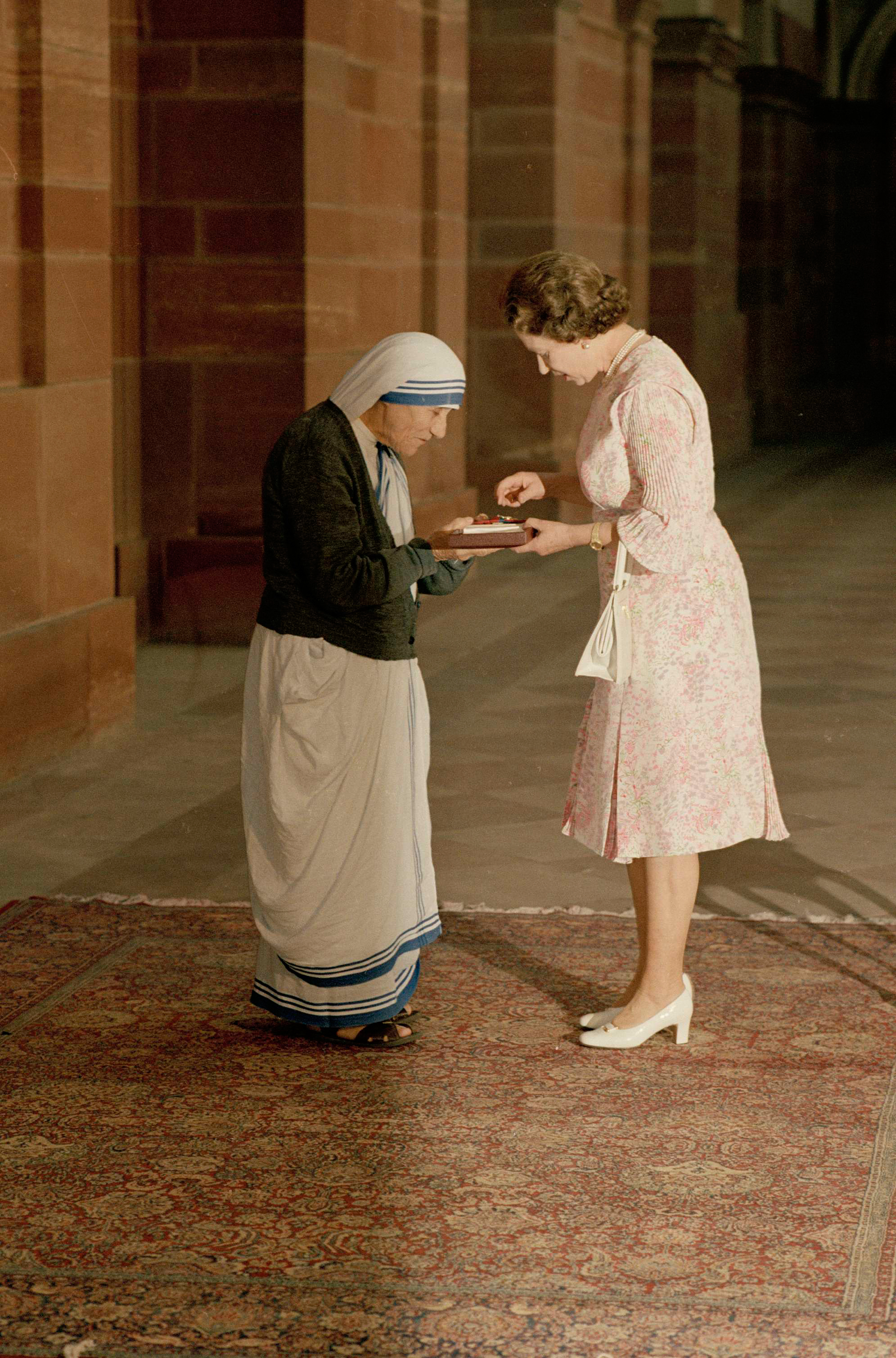 Queen Elizabeth II and Mother Teresa look at the Insignia of the Honorary Order of Merit, which she just presented to the Lady of Calcutta, at the Rashtrapati Shavar in New Delhi, India, on Nov. 24, 1983.