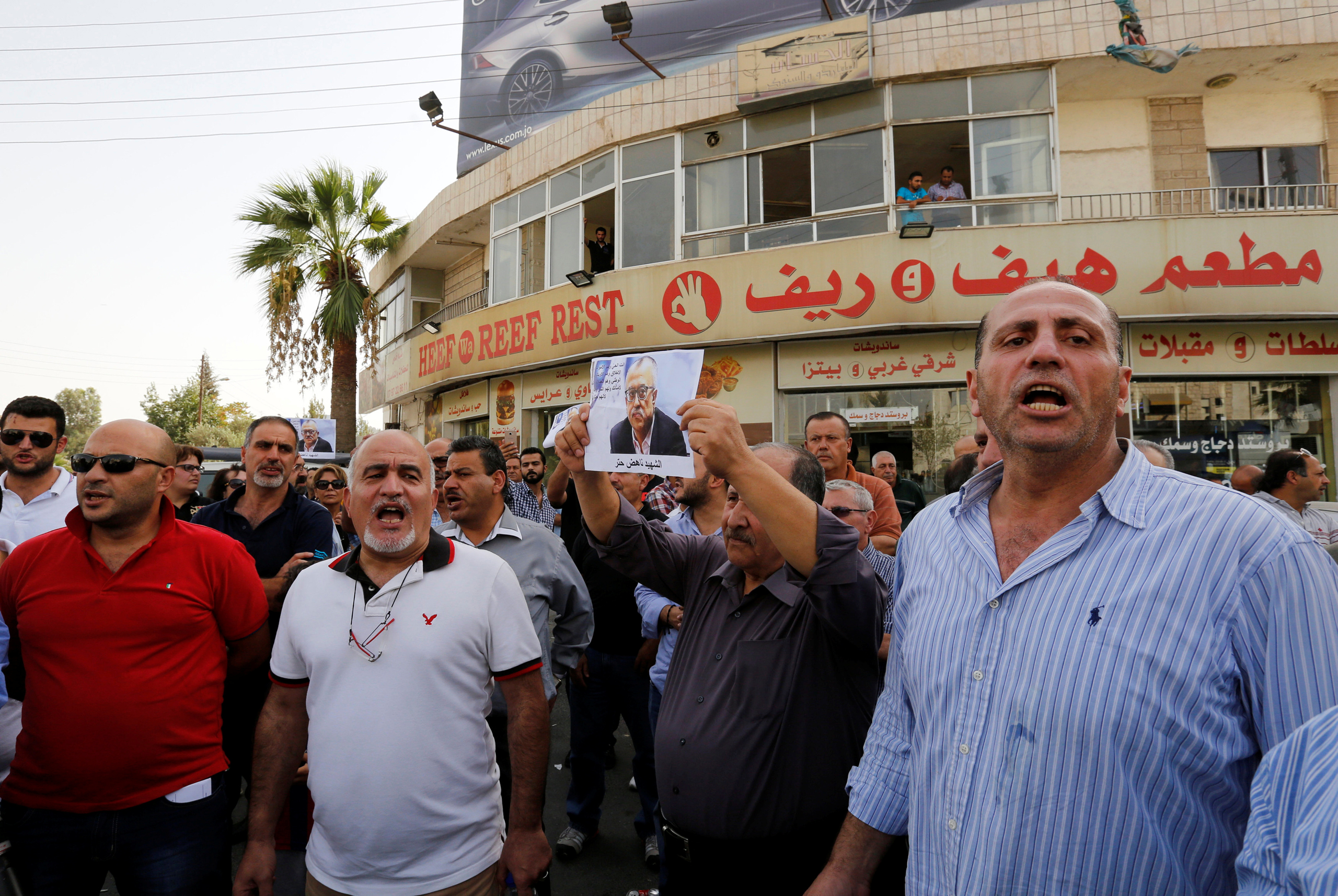 Relatives and friends of the Jordanian writer Nahed Hattar hold pictures of him and chant slogans against the government during a sit-in in the town of Al-Fuheis, Jordan, on Sept. 25, 2016.