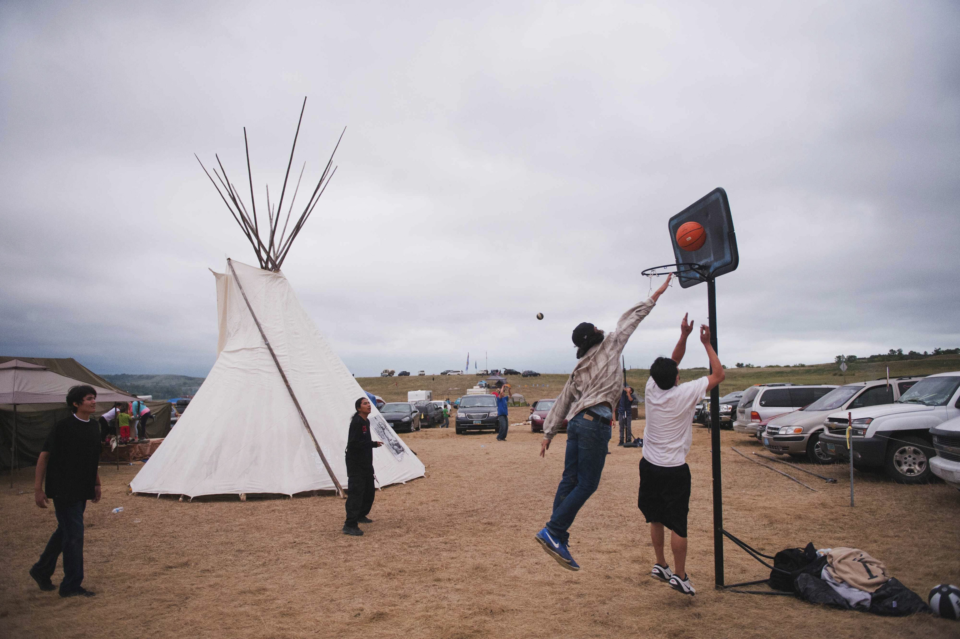 Native American protesters play basketball in an encampment that has grown on the banks of the Cannon Ball River  in Cannon Ball, North Dakota, on Sept. 5, 2016.