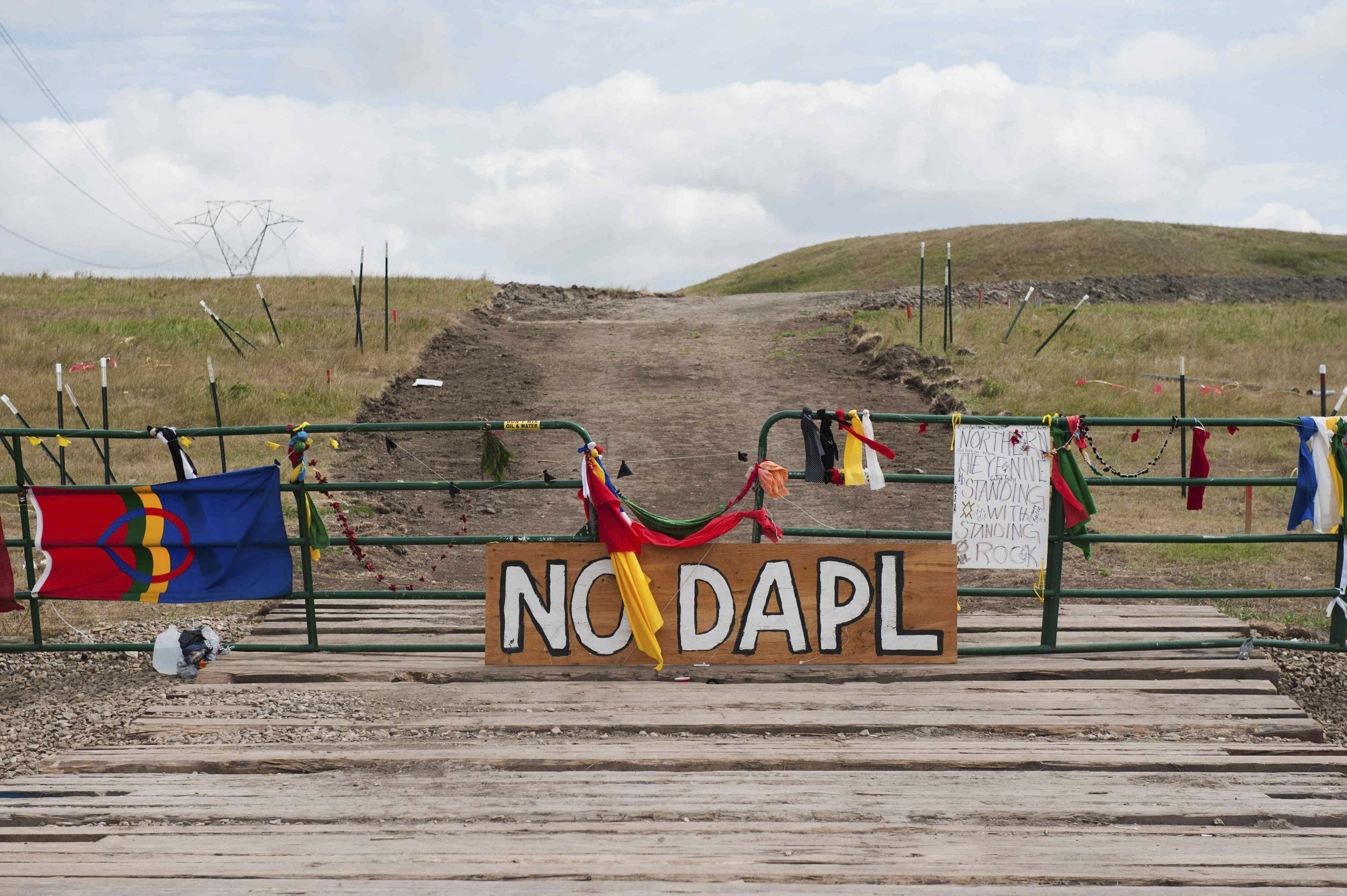 Signs left by protesters demonstrating against the Energy Transfer Partners Dakota Access oil pipeline sit at the gate of a construction access road in Cannon Ball, North Dakota, on Sept. 6, 2016.