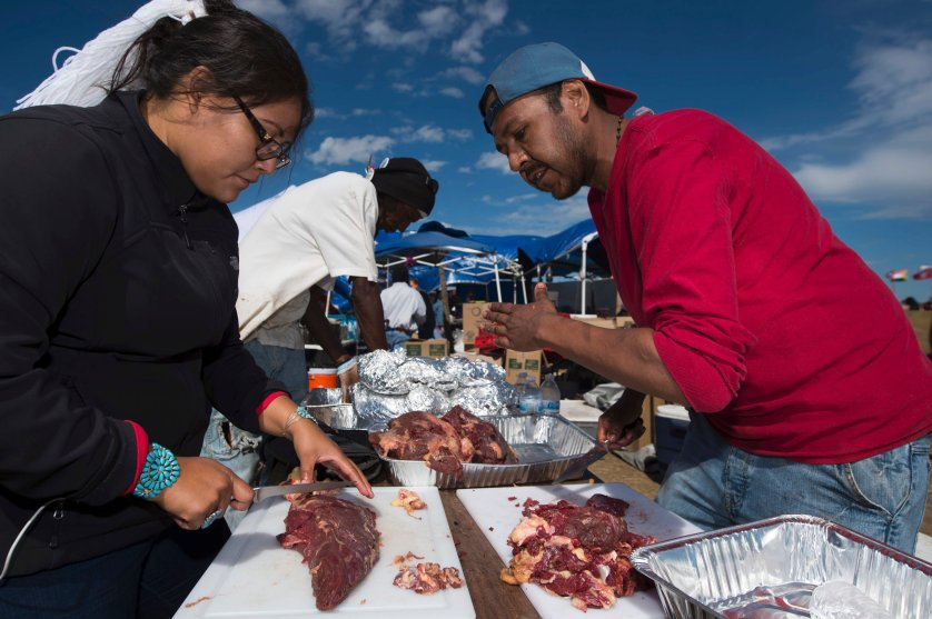 Lamar Armstrong of the Mojave Paiute, right, instructs graduate student Tyesha Ignacio of the Najavo Nation how to prepare donated bison meat in the main kitchen area of the Standing Rock Sioux protest encampment near Cannon Ball, North Dakota on Sept. 3, 2016.