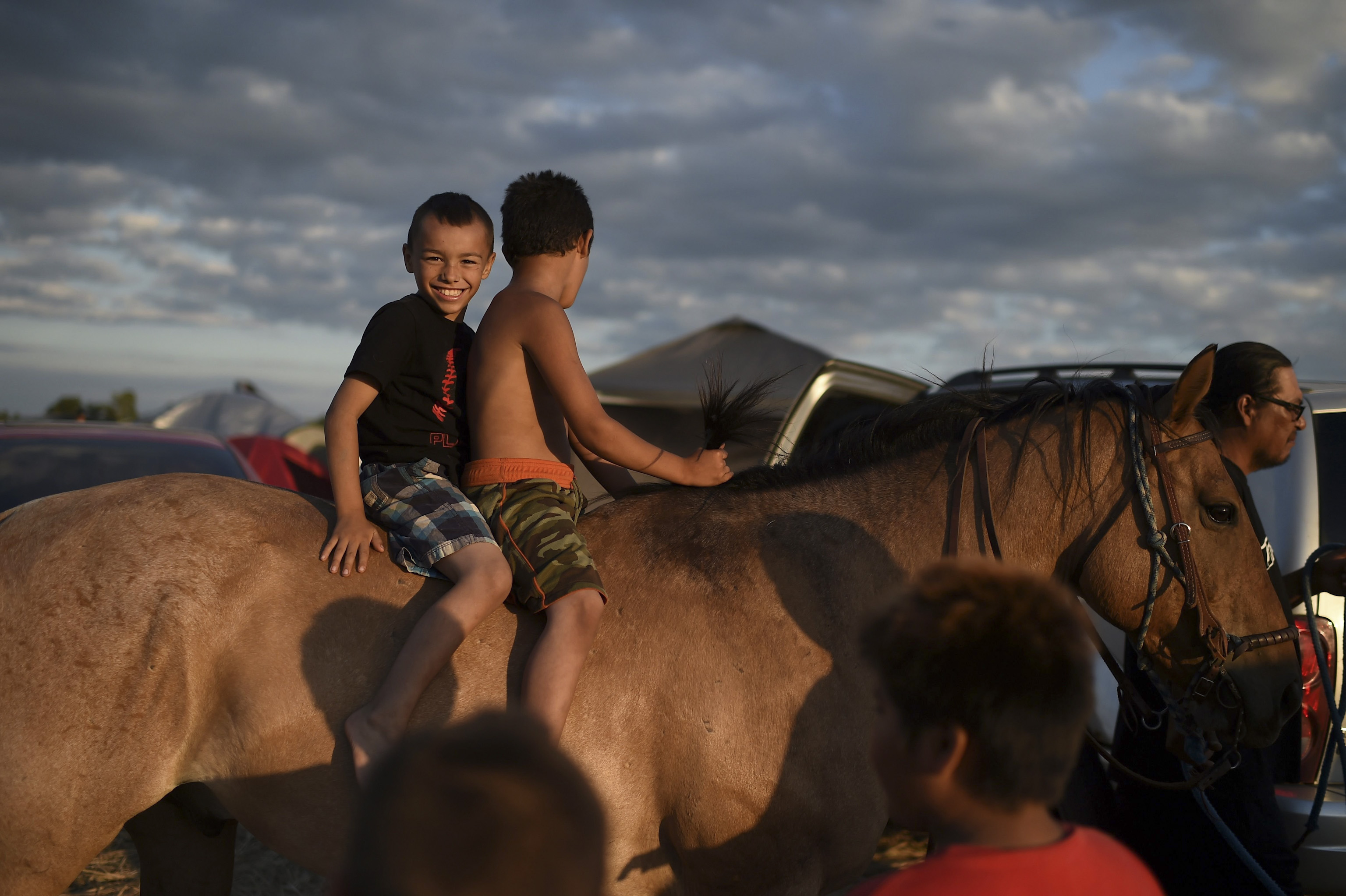 Boys enjoy a later afternoon horseback ride at an encampment where hundreds of people gathered to join the Standing Rock Sioux Tribe's protest against the construction of the Dakota Access Pipe (DAPL), near Cannon Ball, North Dakota, September 3, 2016.