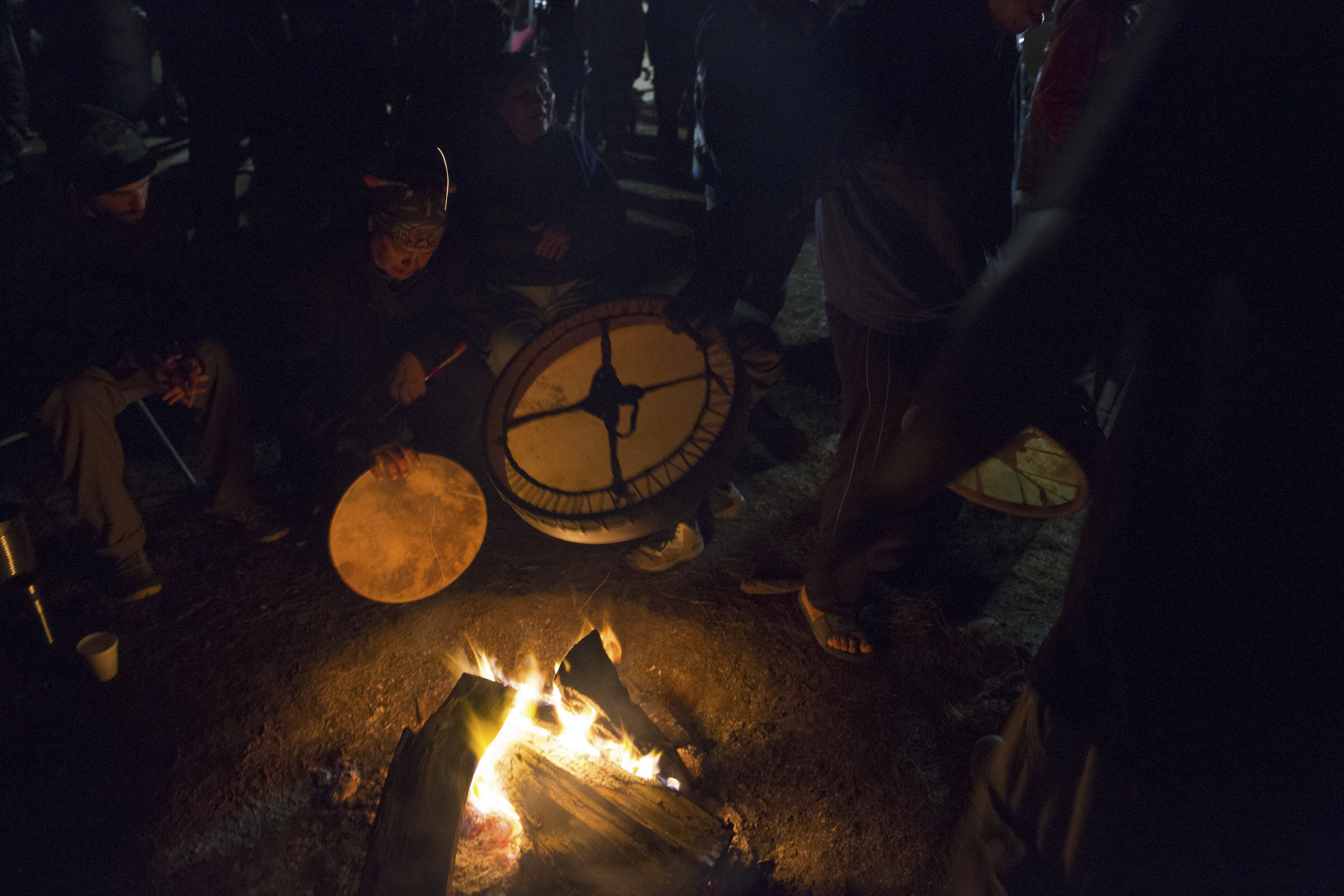 Drummers warm up their instruments over the fire Sacred Stone Camp, North Dakota, on Sept. 8, 2016.
