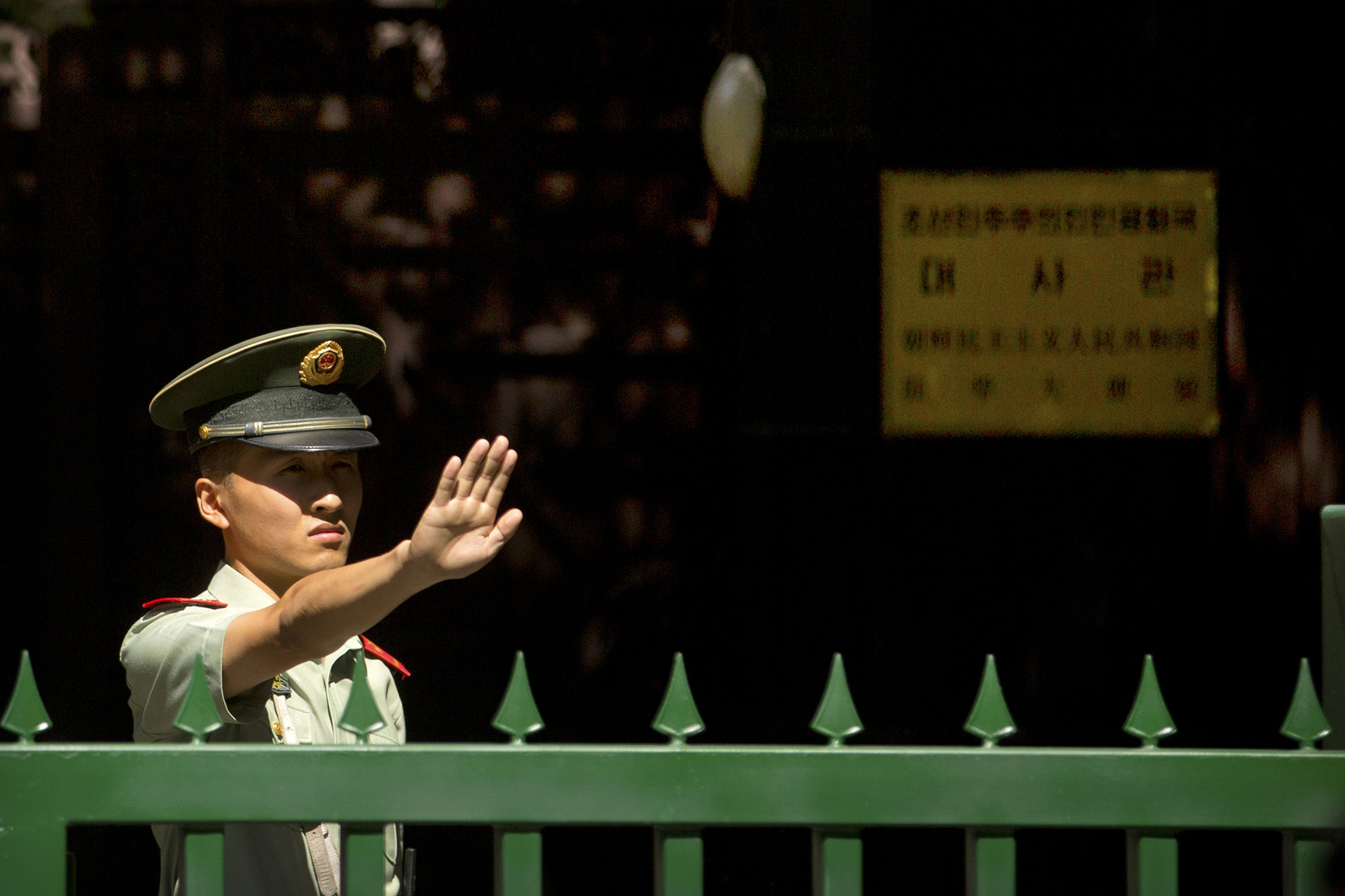 A Chinese paramilitary policeman holds his hand up outside the North Korean embassy in Beijing, Sept. 9, 2016.