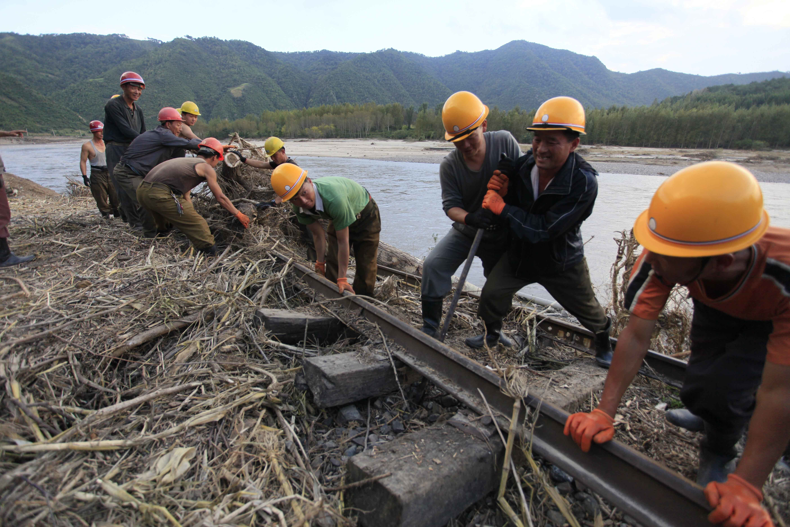 Workers repair the flood-damaged train track between Sinjon and Kanphyong train stations in North Hamgyong Province, North Korea, on Sept. 16, 2016.