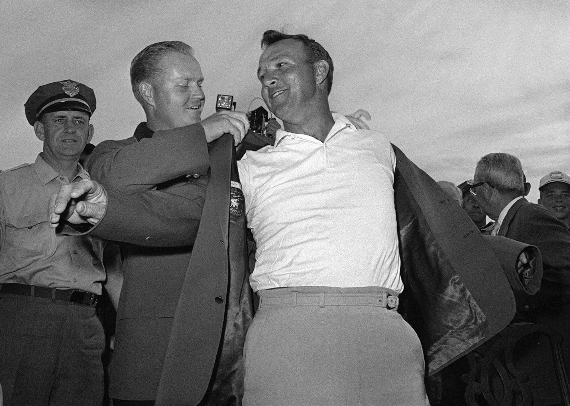 In this April 12, 1964 file photo, Arnold Palmer, slips into his green jacket with help from Jack Nicklaus after winning the Masters golf championship, in Augusta, Ga.