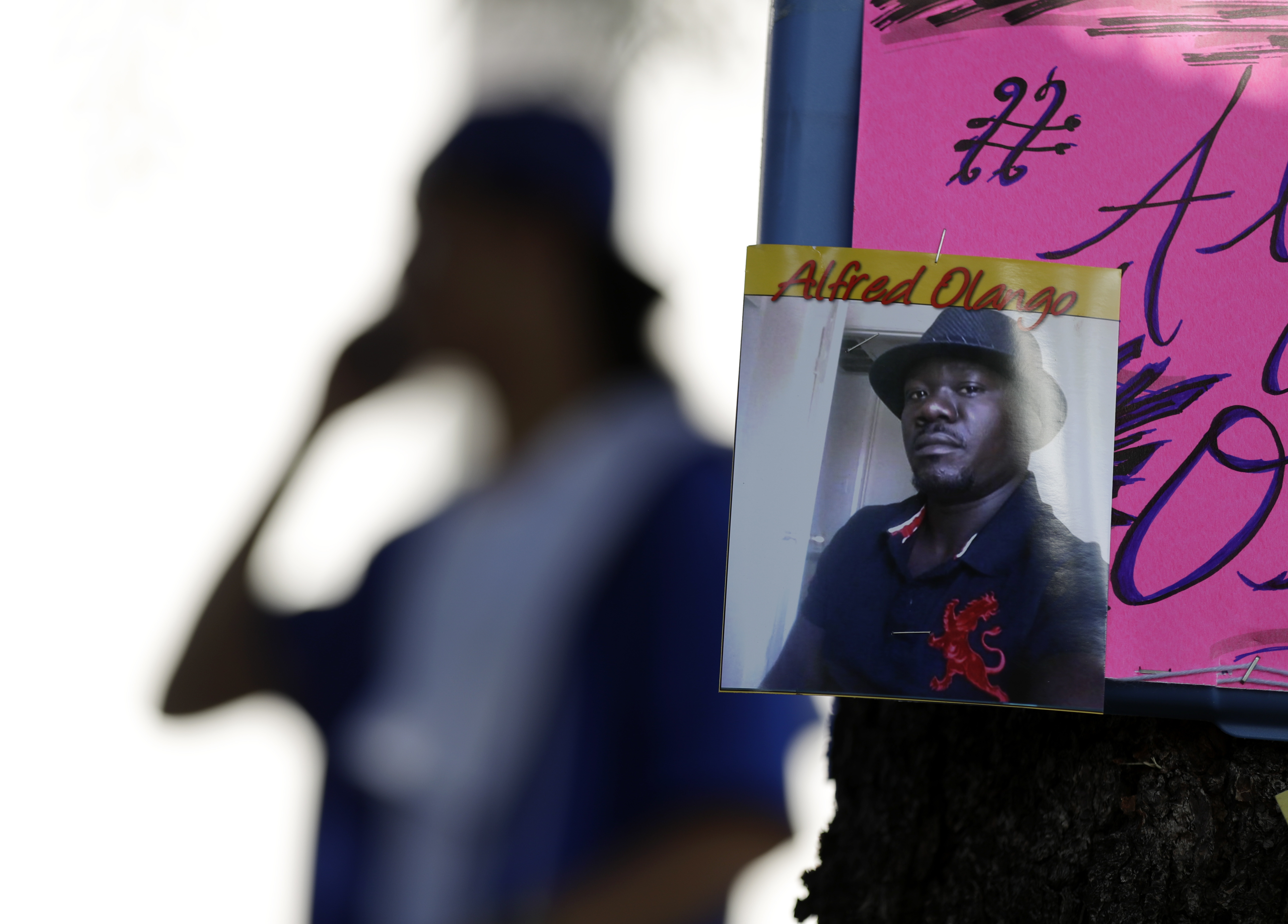 A man stands behind a picture of Alfred Olango during a protest, in El Cajon, Calif., on Sept. 28, 2016.