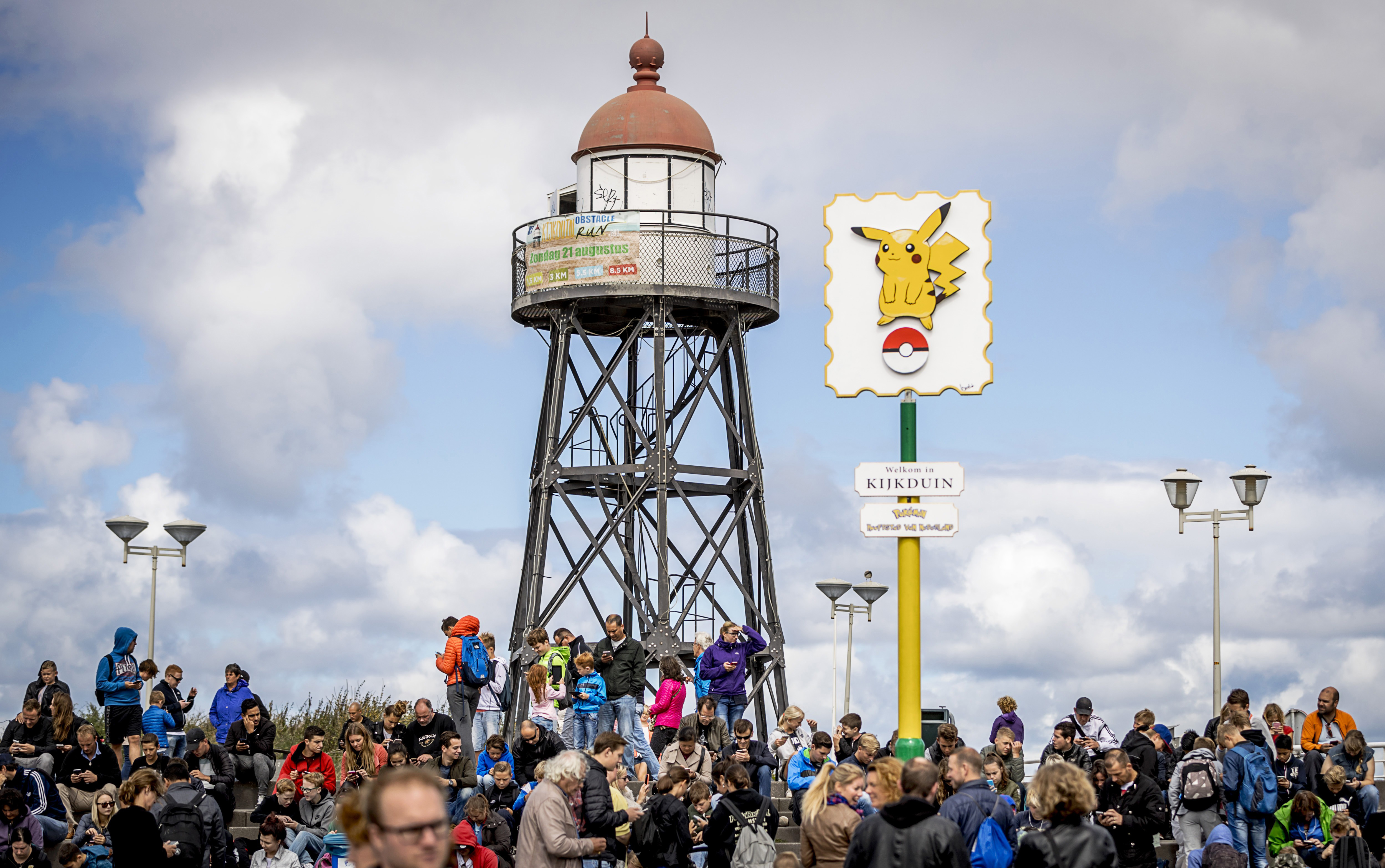 Pokemon Go players look at their cell phones as they gather at the beach in Kijkduin, which has been named as the Pokemon capital of the Netherlands, on August 10, 2016.