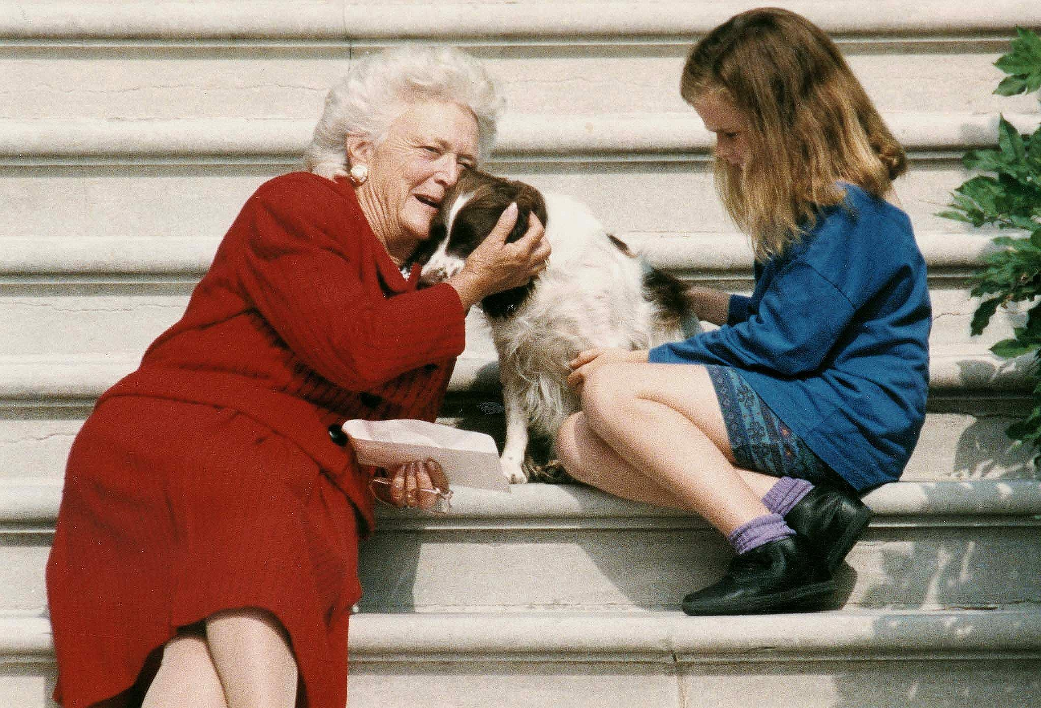Barbara Bush talks to her dog, Millie, as she and granddaughter, Barbara Bush, age nine, wait for George Bush to return to the White House on Sept. 13, 1991,