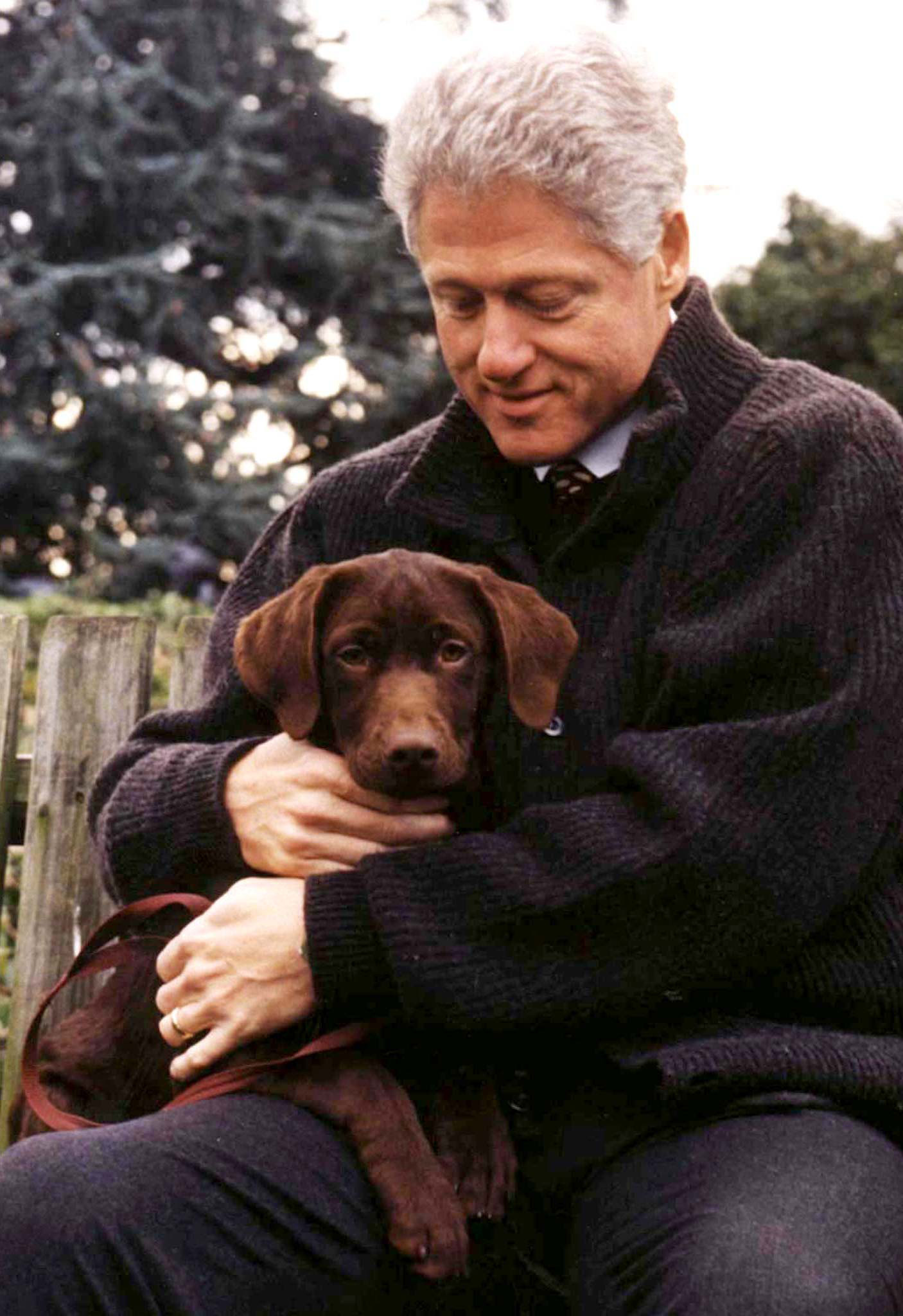 Bill Clinton holds his new dog, a chocolate Labrador pup, in a photo released December 9, 1997.