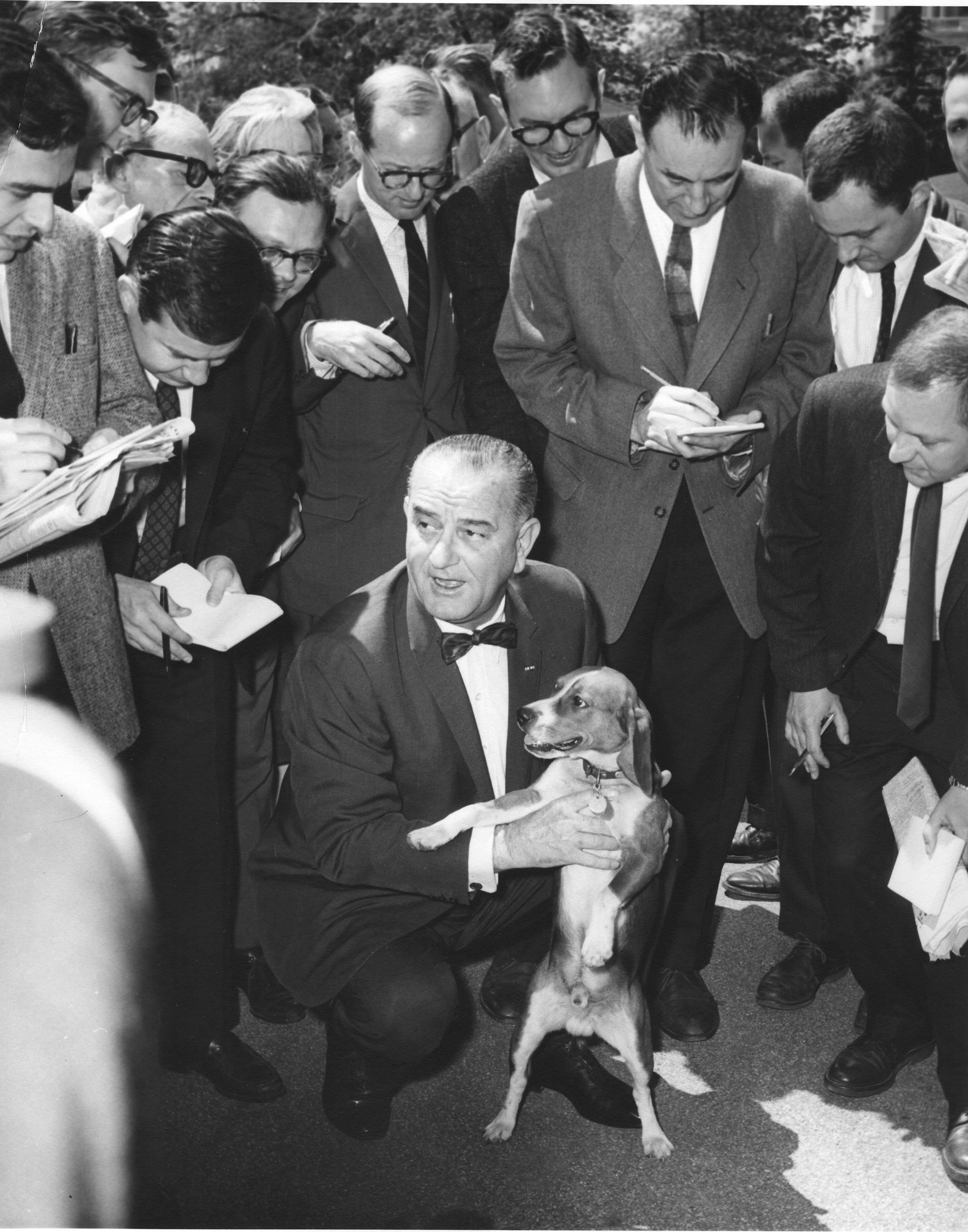 Lyndon Johnson holds one of his beagles, named Him, as he speaks with members of the White House press corps in Washington D.C., May 2 1964.