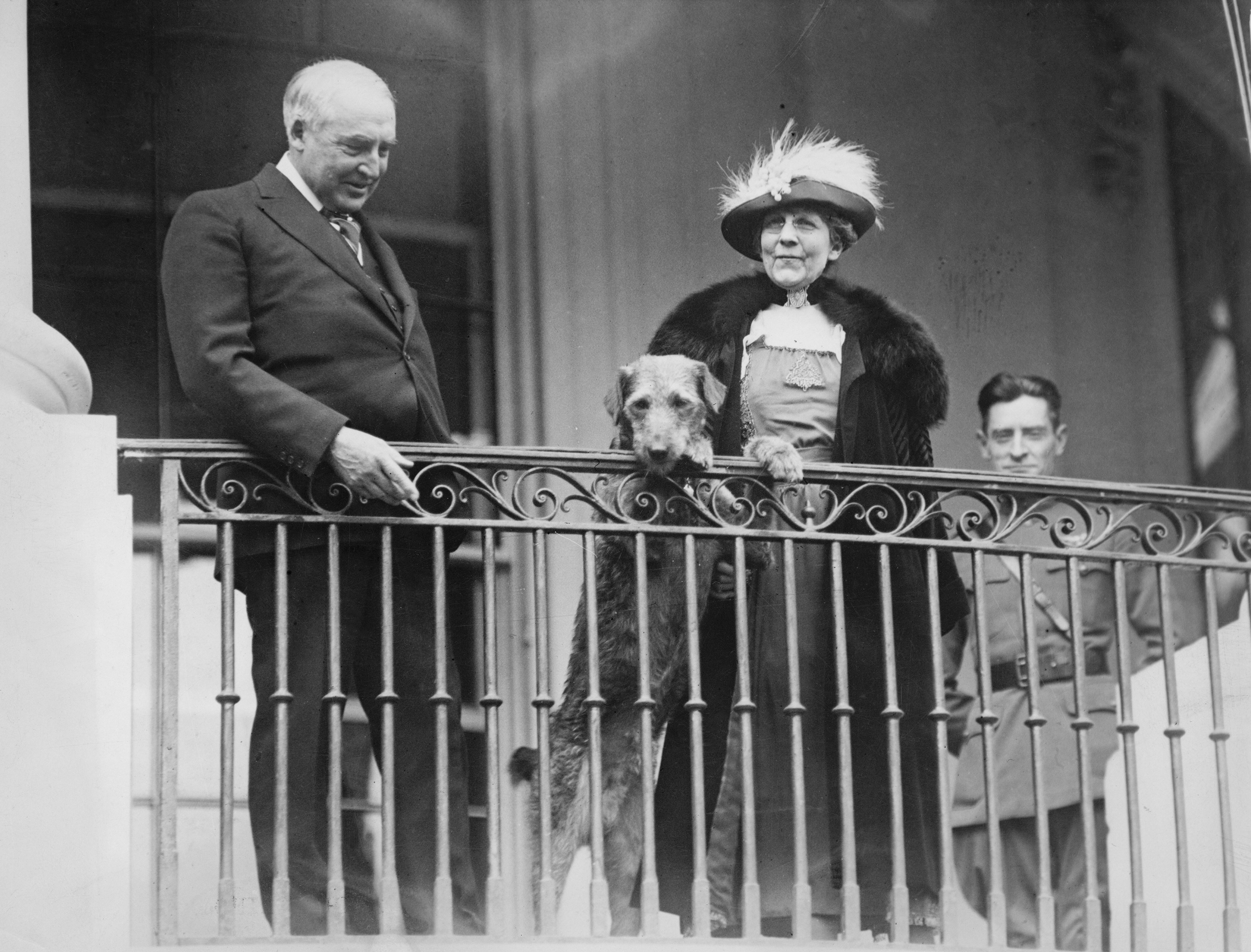 Warren G. Harding, Florence Harding, and their dog, Laddie Boy, watch from a balcony as an annual Easter Monday children's egg-rolling event takes place on the White House lawn, circa 1922.
