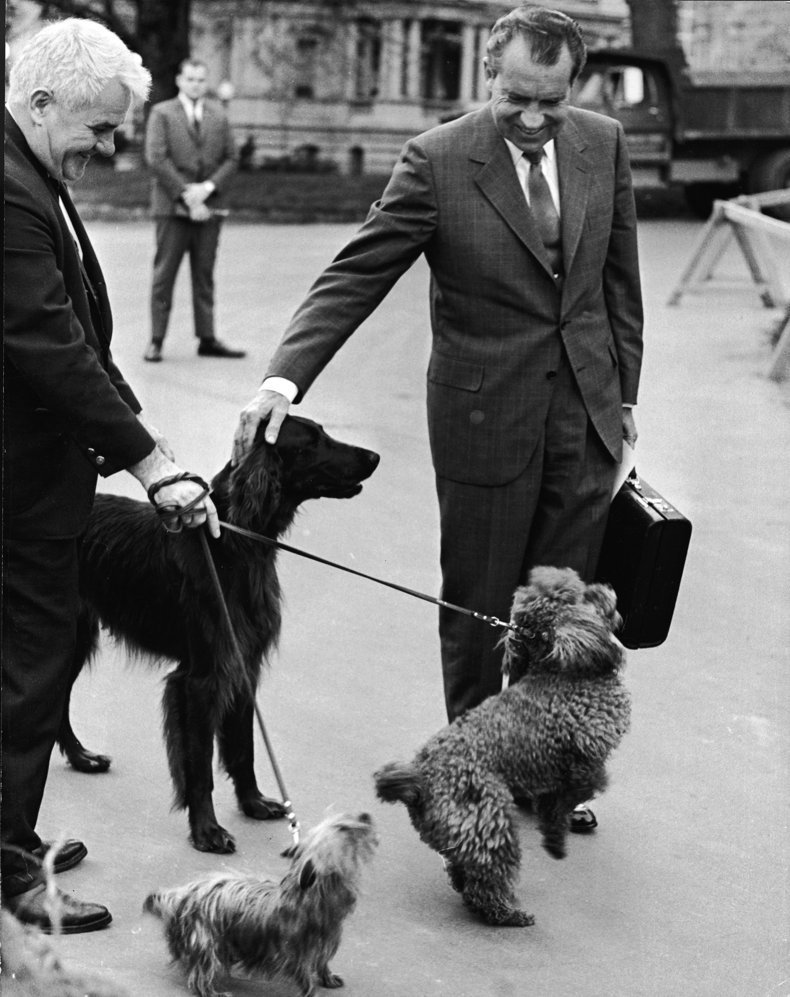 Richard M. Nixon pets his dogs, Irish Setter 'King Timahoe,' Yorkshire Terrier 'Pasha' and French Poodle 'Vicky,' outside the White House on April 30, 1970.