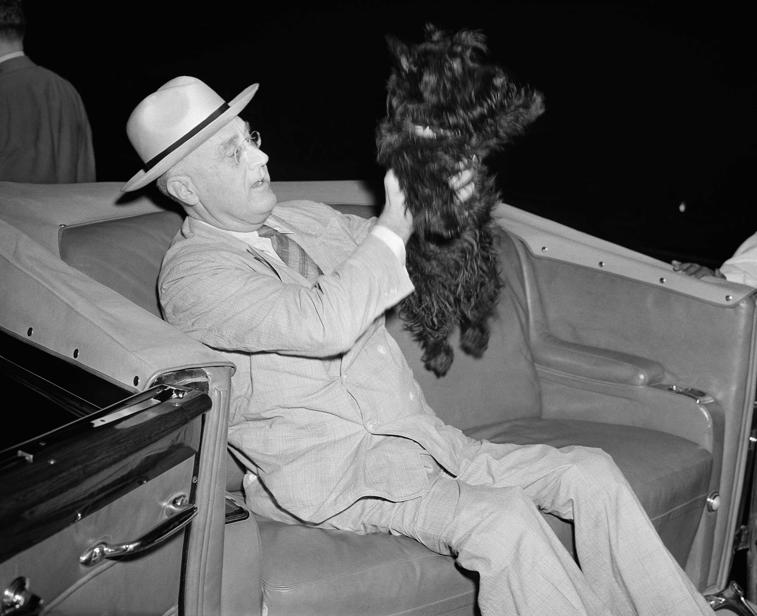 Franklin D. Roosevelt lifts his dog, Fala, as he prepares to motor from his special train to the Yacht Potomac in New London, Connecticut, Aug. 3, 1941.
