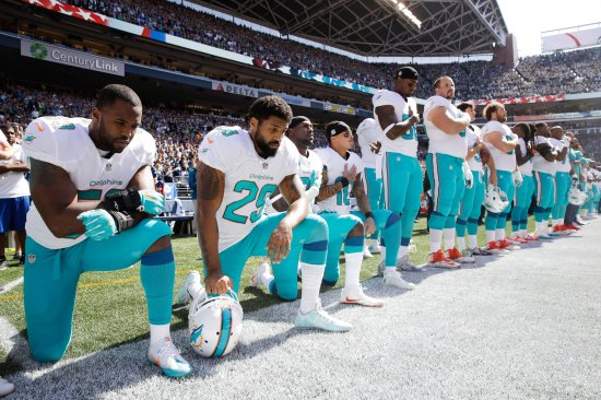 From left, Miami Dolphins Jelani Jenkins, Arian Foster, Michael Thomas and Kenny Stills kneel during the national anthem on Sept. 11