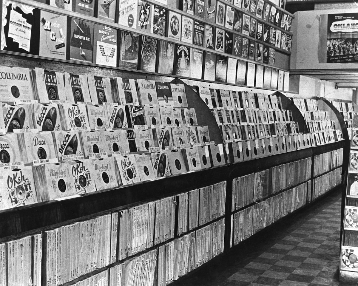 An interior view of a record store from the 1950's which shows albums with various record company labels