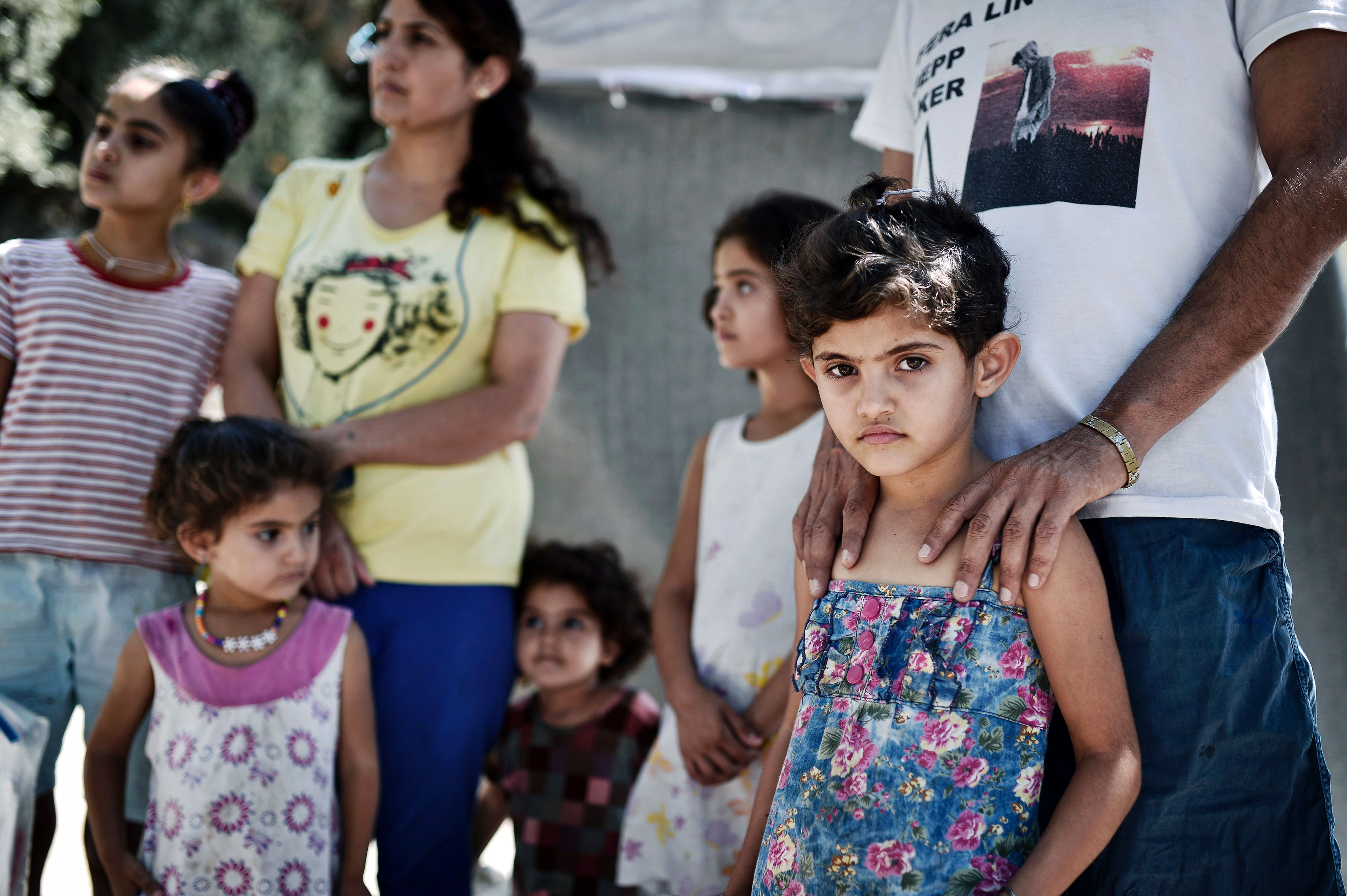 Ando Elias Tareq, a Yezidi from Sinjar in Iraq, stands behind his daughter outside the Samos hotspot where they live on Sept. 1, 2016.