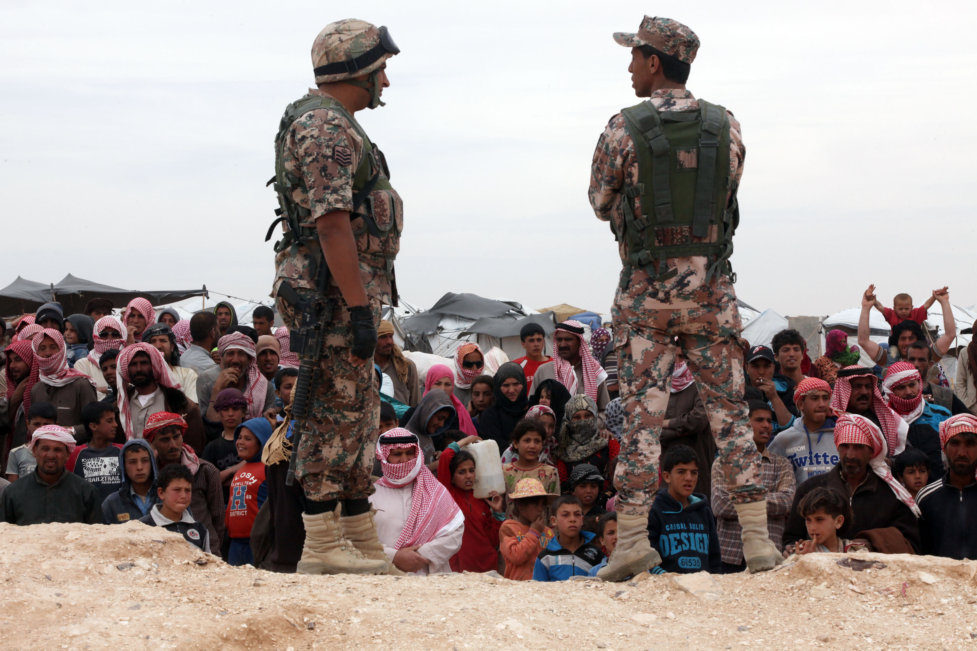 Soldiers stand near Syrian refugees who have arrived at the Jordanian military crossing point of Hadalat at the border with Syria after a long walk through the Syrian desert in Hadalat, Jordan, on May 4, 2016.