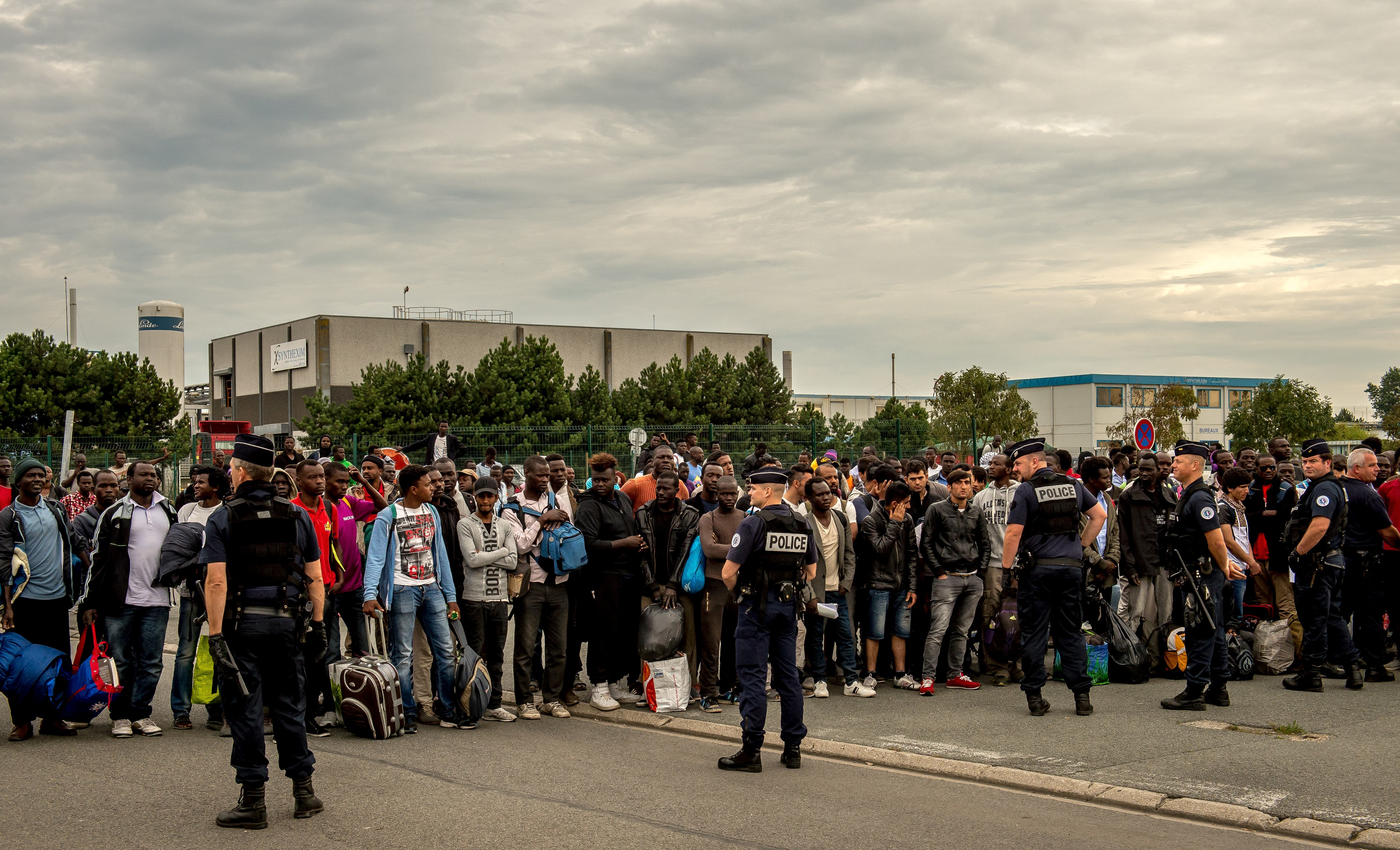 Migrants from the 'Jungle' migrant camp who have been denied access to a bus heading to a  Welcome and orientation centre  (CAO) are gathered under police surveillance, in Calais on Sept. 13, 2016.