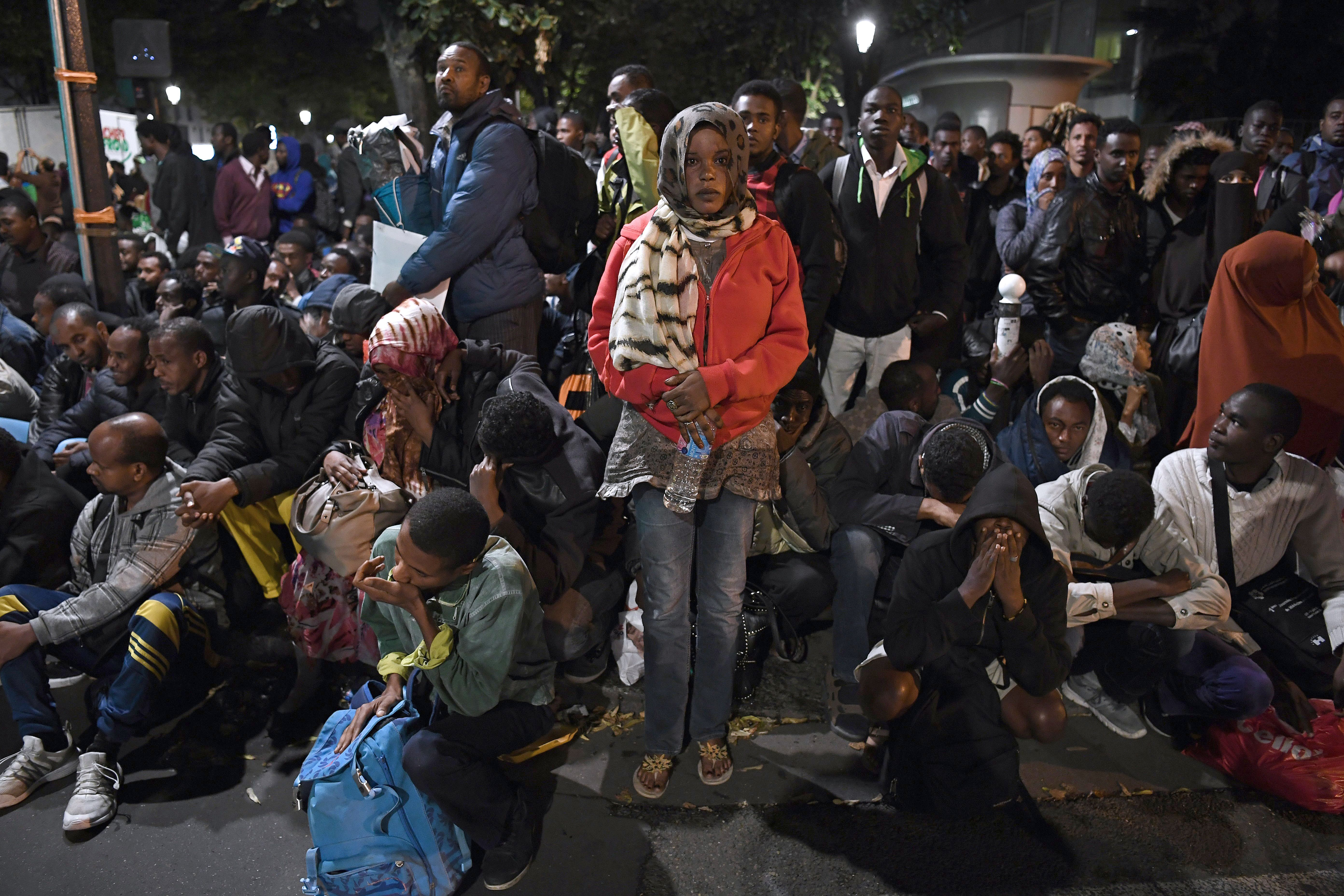 Migrants gather and wait before being evacuated from a makeshift migrant camp set up between the metro stations of Jaures and Stalingrad, in Paris on Sept. 16, 2016.