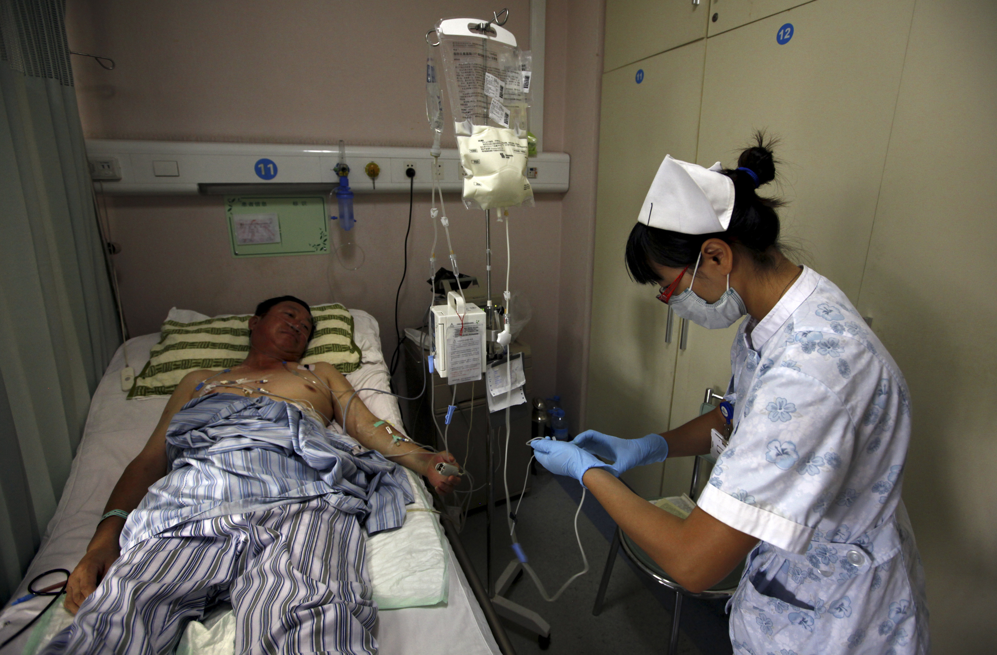 A nurse prepares to inject a cancer patient with medicine as she performs her daily rounds at the Beijing Cancer Hospital in this file photo from 2011. Cancer is spreading in China and kills millions annually