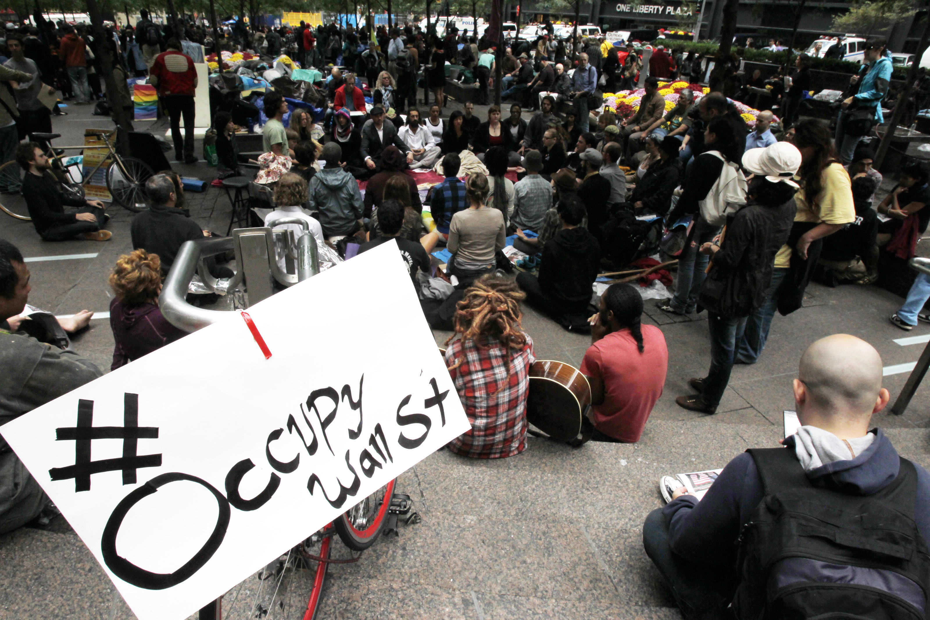 Occupy Wall Street protesters meditate while a sign bearing their Twitter handle hangs from a railing in Zuccotti Park in New York City, Oct. 1, 2011.